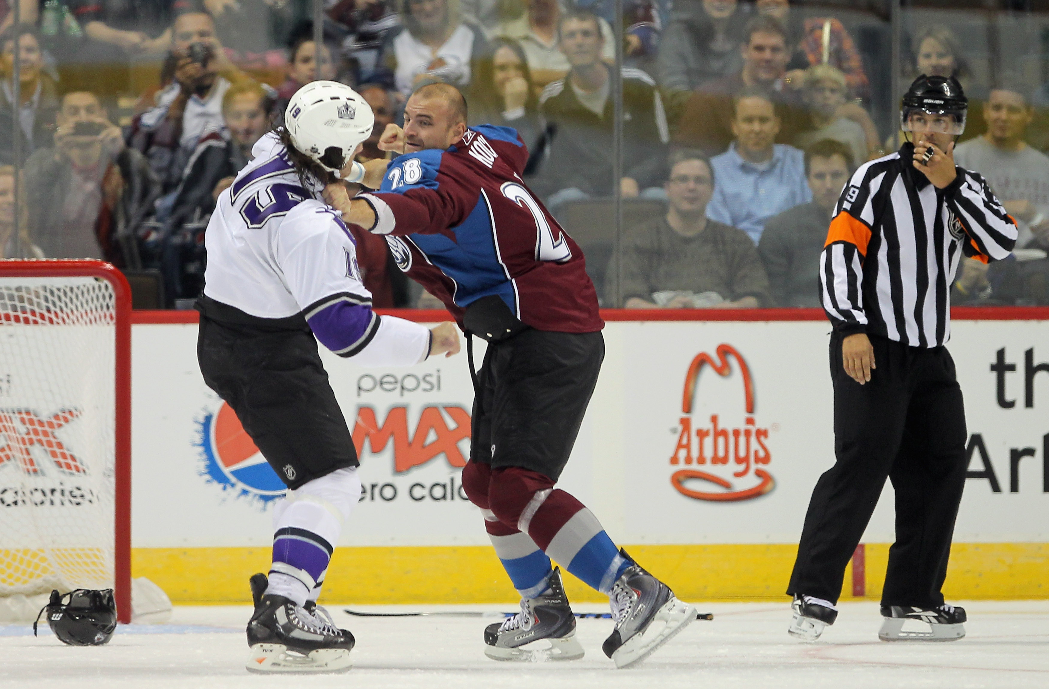DENVER - SEPTEMBER 22:  John Zeiler #13 of the Los Angeles Kings and David Koci #28 of the Colorado Avalanche engage in a fight as referee Ghislain Hebert watches during preseason NHL action at the Pepsi Center on September 22, 2010 in Denver, Colorado. T