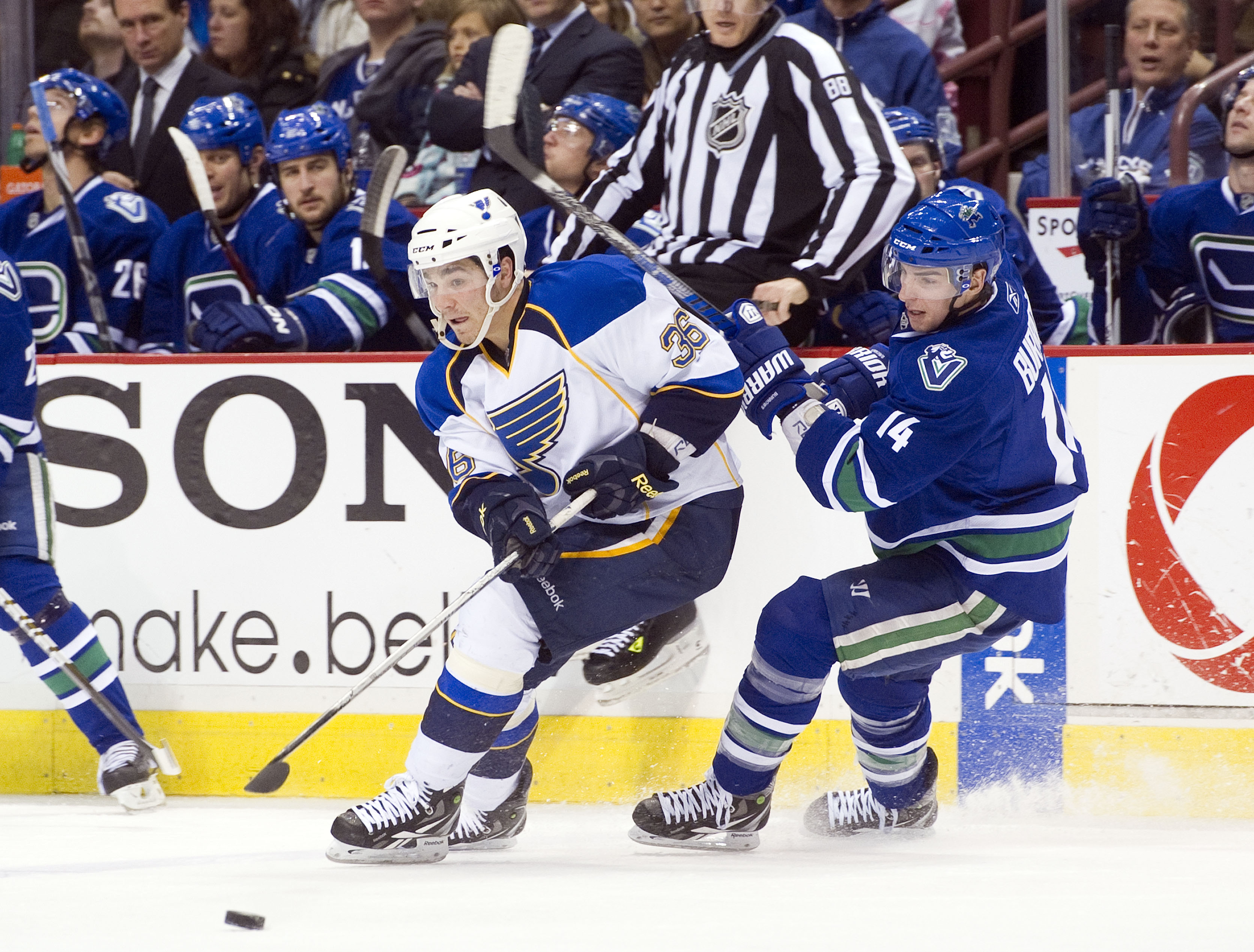 VANCOUVER, CANADA - DECEMBER 5: Alexandre Burrows #14 of the Vancouver Canucks checks Matt D'Agostini #36 of the St Louis Blues off the puck during the third period in NHL action on December 05, 2010 at Rogers Arena in Vancouver, BC, Canada.  (Photo by Ri
