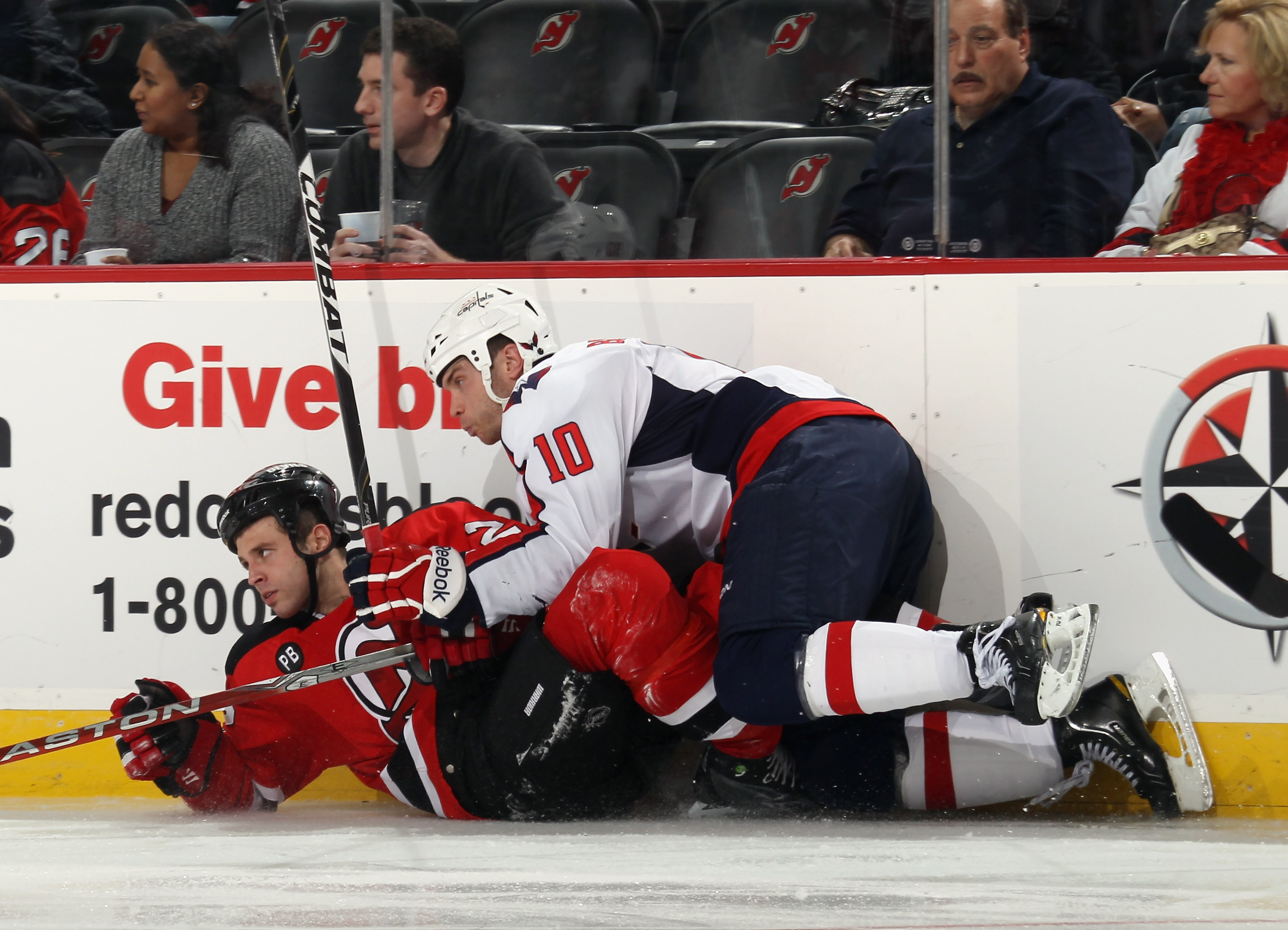 NEWARK, NJ - NOVEMBER 22: Matthew Corrente #22 of the New Jersey Devils is taken down by Matt Bradley #10 of the Washington Capitals at the Prudential Center on November 22, 2010 in Newark, New Jersey.  (Photo by Bruce Bennett/Getty Images)
