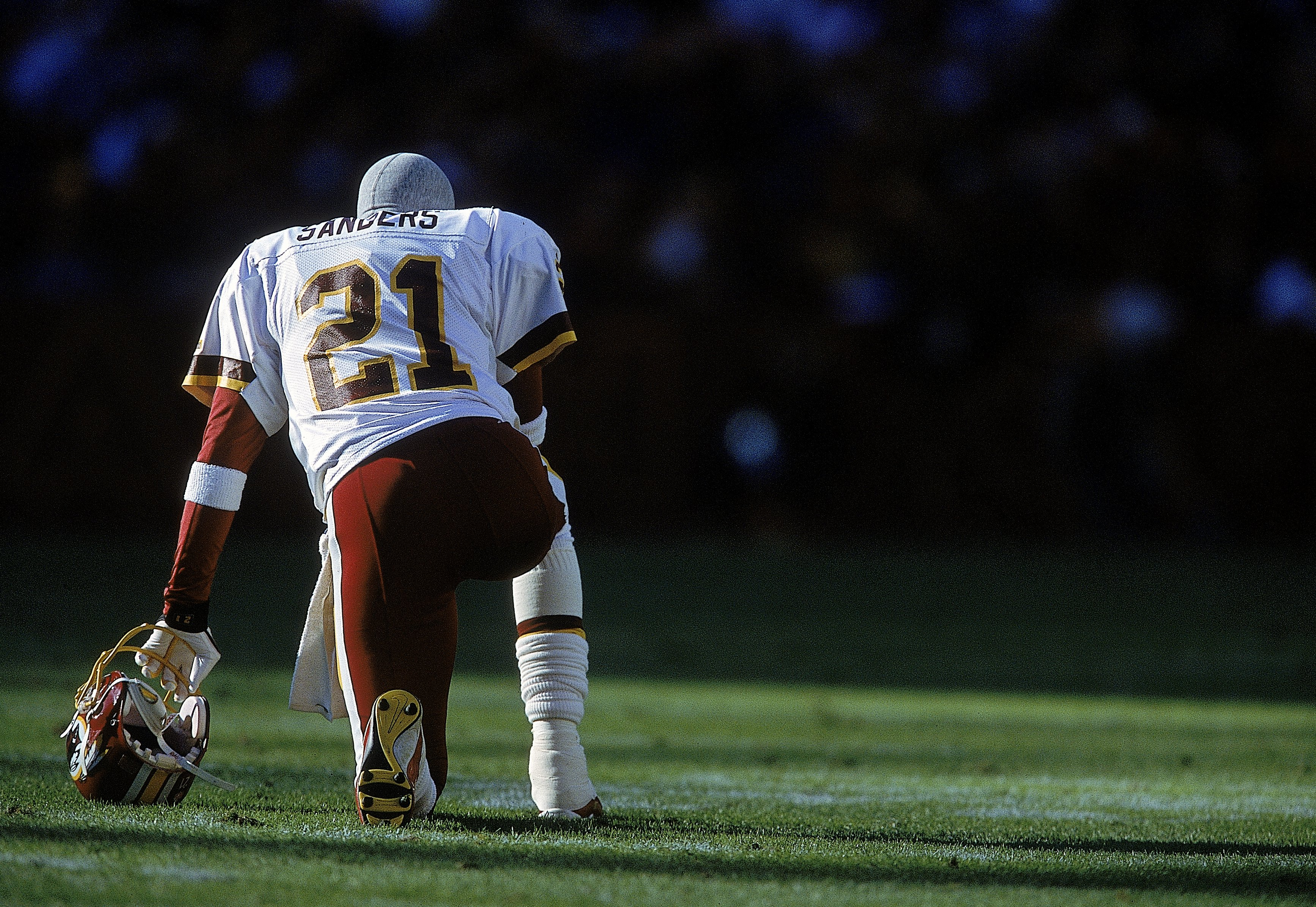 26 Nov 2000: Deion Sanders #21 of the Washington Redskins kneels on the field before the game against the Philadelphia Eagles at the FedEx Field in Landover, Maryland. The Eagles defeated the Redskins 23-20.Mandatory Credit: Jamie Squire  /Allsport