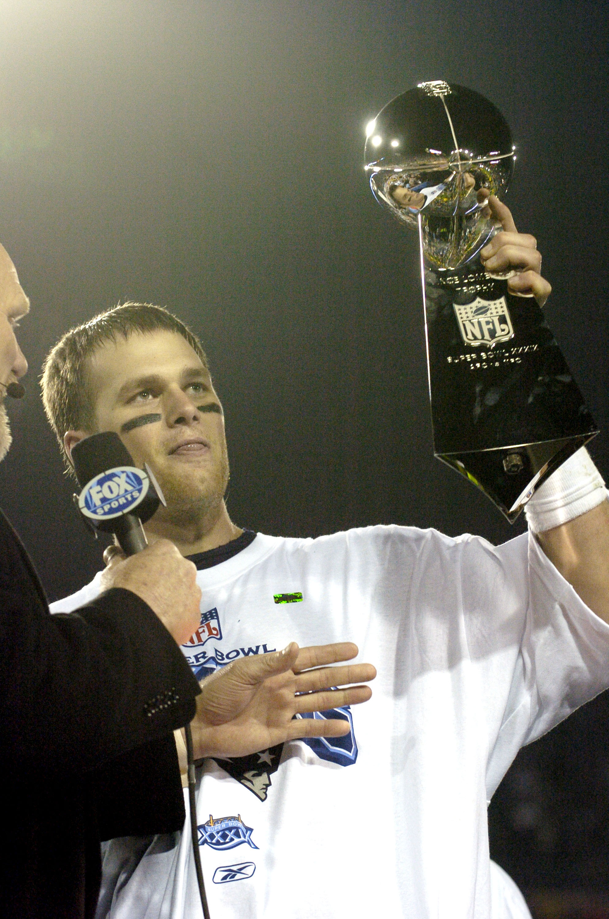 Tom Brady holds the Vince Lombardi Trophy as he stands on the podium after The New England Patriots defeated The Philadelphia Eagles in Super Bowl XXXIX at Alltel Staduim in Jacksonville, Florida. (Photo by A. Messerschmidt/Getty Images)