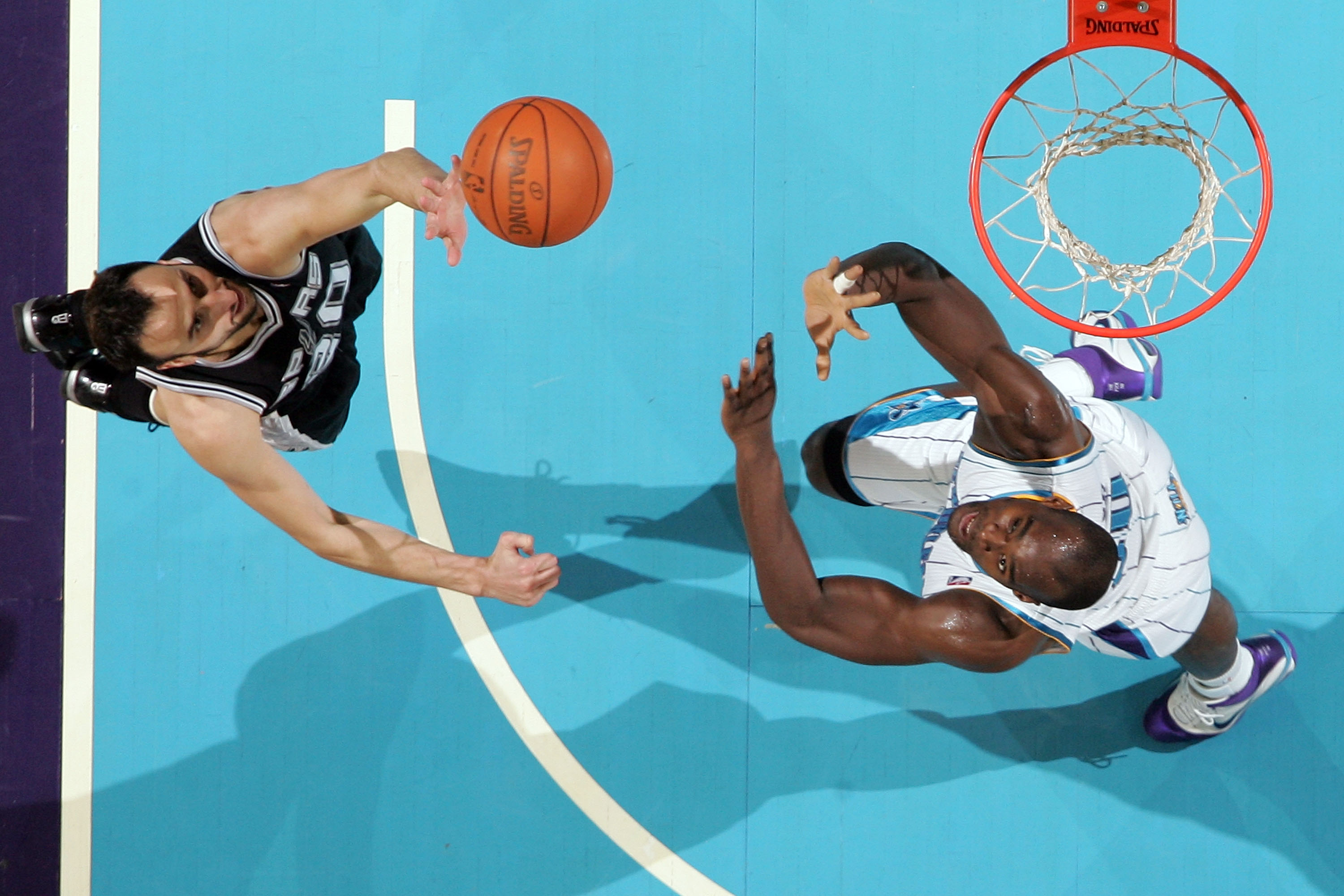 NEW ORLEANS - NOVEMBER 28:  Manu Ginobili #20 of the San Antonio Spurs shoots the ball over Emeka Okafor #50 of the New Orleans Hornets at the New Orleans Arena on November 28, 2010 in New Orleans, Louisiana.  The Spurs defeated the Hornets 109-95.  NOTE