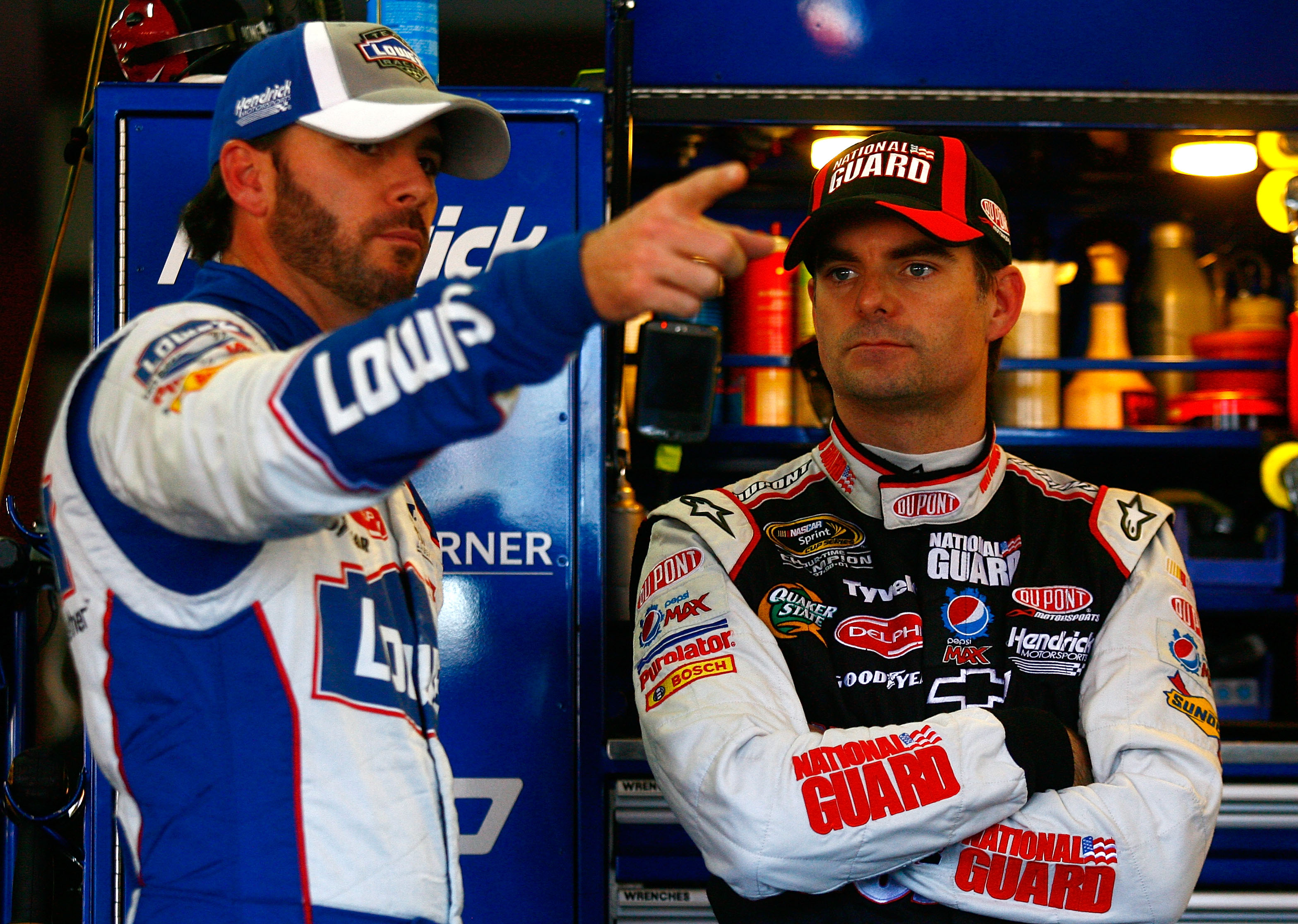 TALLADEGA, AL - OCTOBER 29:  Jimmie Johnson (L), driver of the #48 Lowe's Chevrolet, talks with Jeff Gordon, driver of the #24 DuPont/National Guard Chevrolet, in the garage during practice for the NASCAR Sprint Cup Series AMP Energy Juice 500 at Talladeg