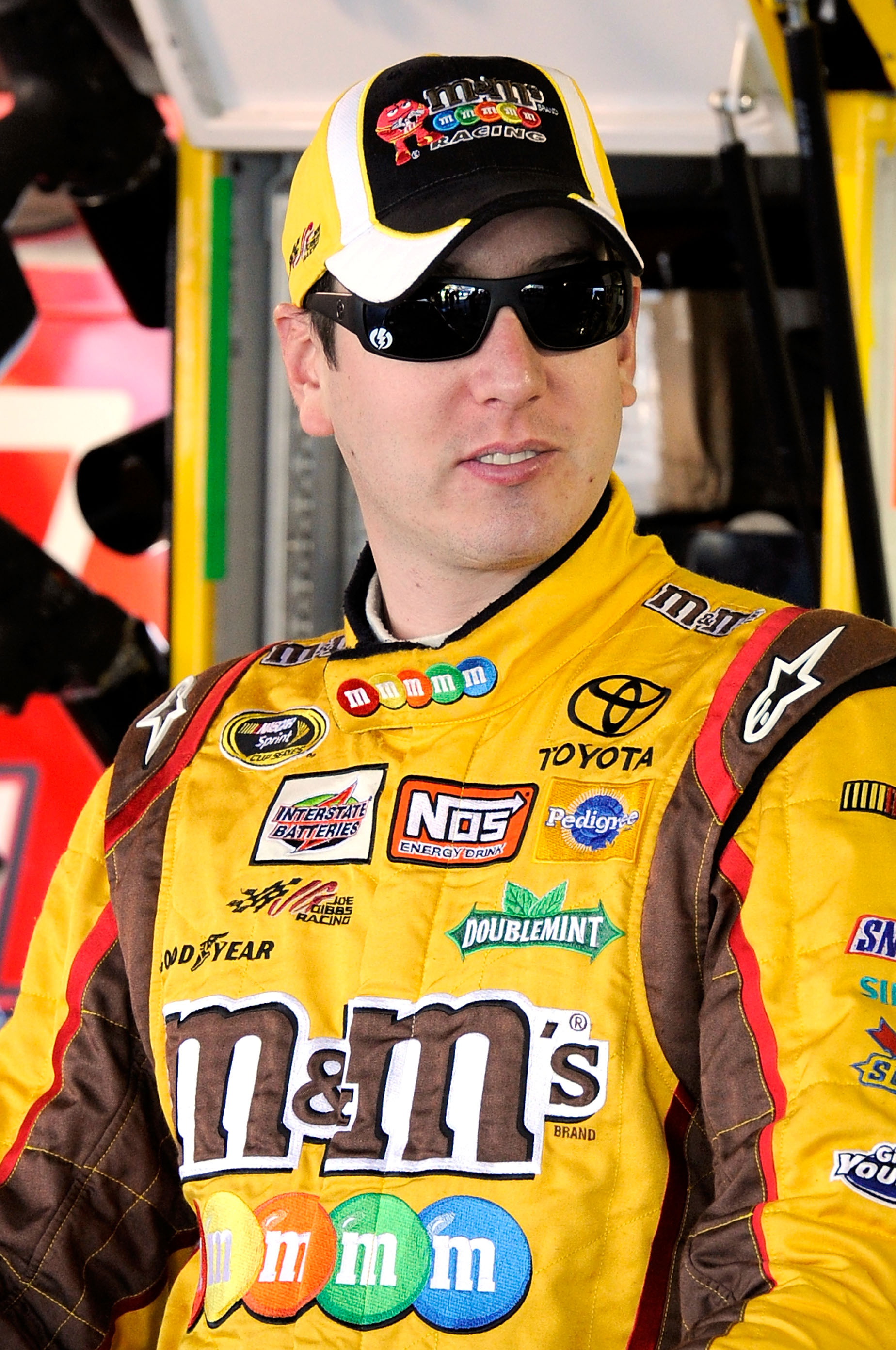 MARTINSVILLE, VA - OCTOBER 22:  Kyle Busch, driver of the #18 M&M's Toyota, stands in the garage prior to practice for the NASCAR Sprint Cup Series TUMS Fast Relief 500 at Martinsville Speedway on October 22, 2010 in Martinsville, Virginia.  (Photo by Joh