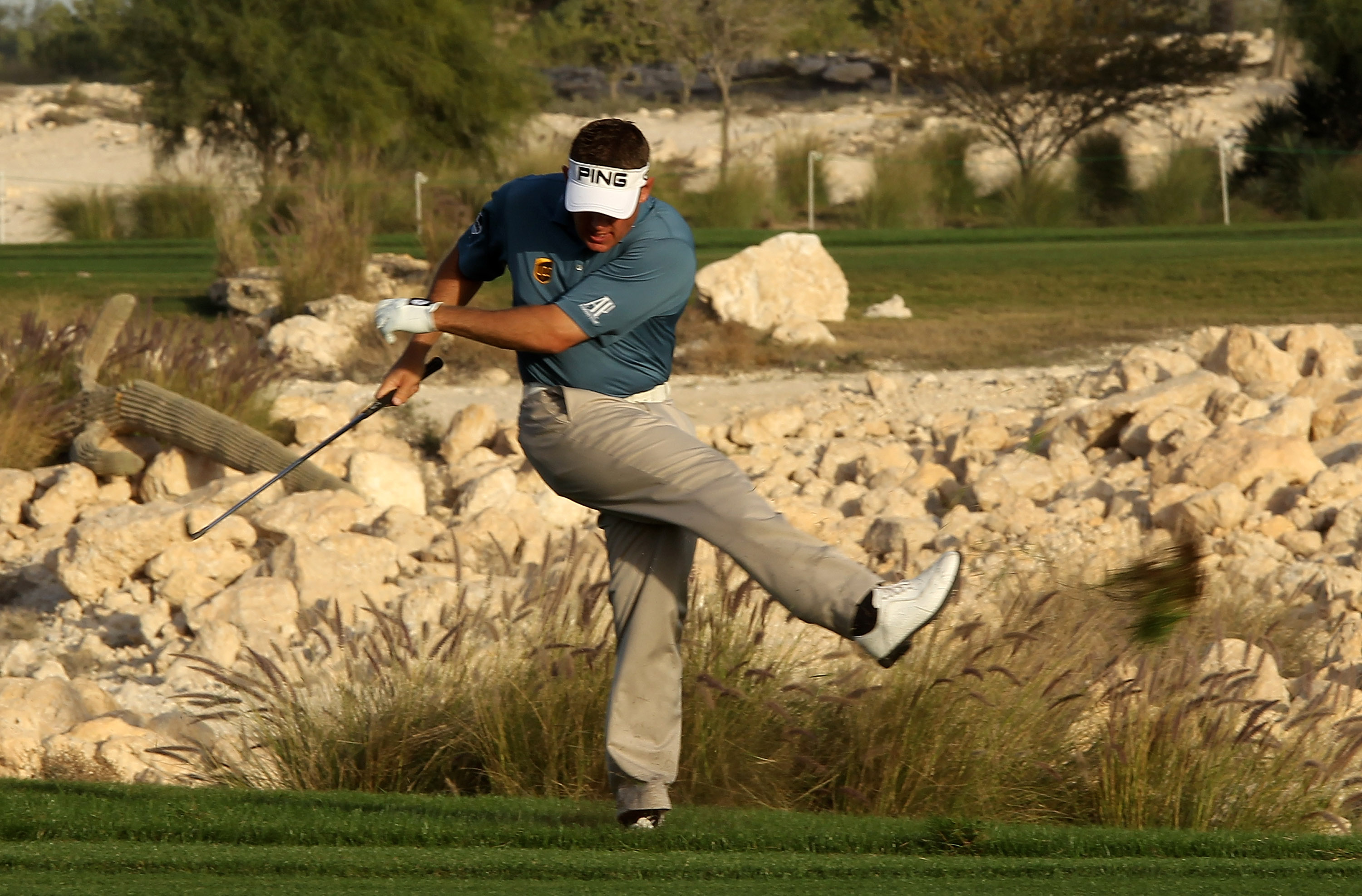 DOHA, QATAR - JANUARY 30:  Lee Westwood of England shows his frustration by kicking up a clump of grass after his second shot on the 18th hole during the third round of the Commercialbank Qatar Masters at Doha Golf Club on January 30, 2010 in Doha, Qatar.