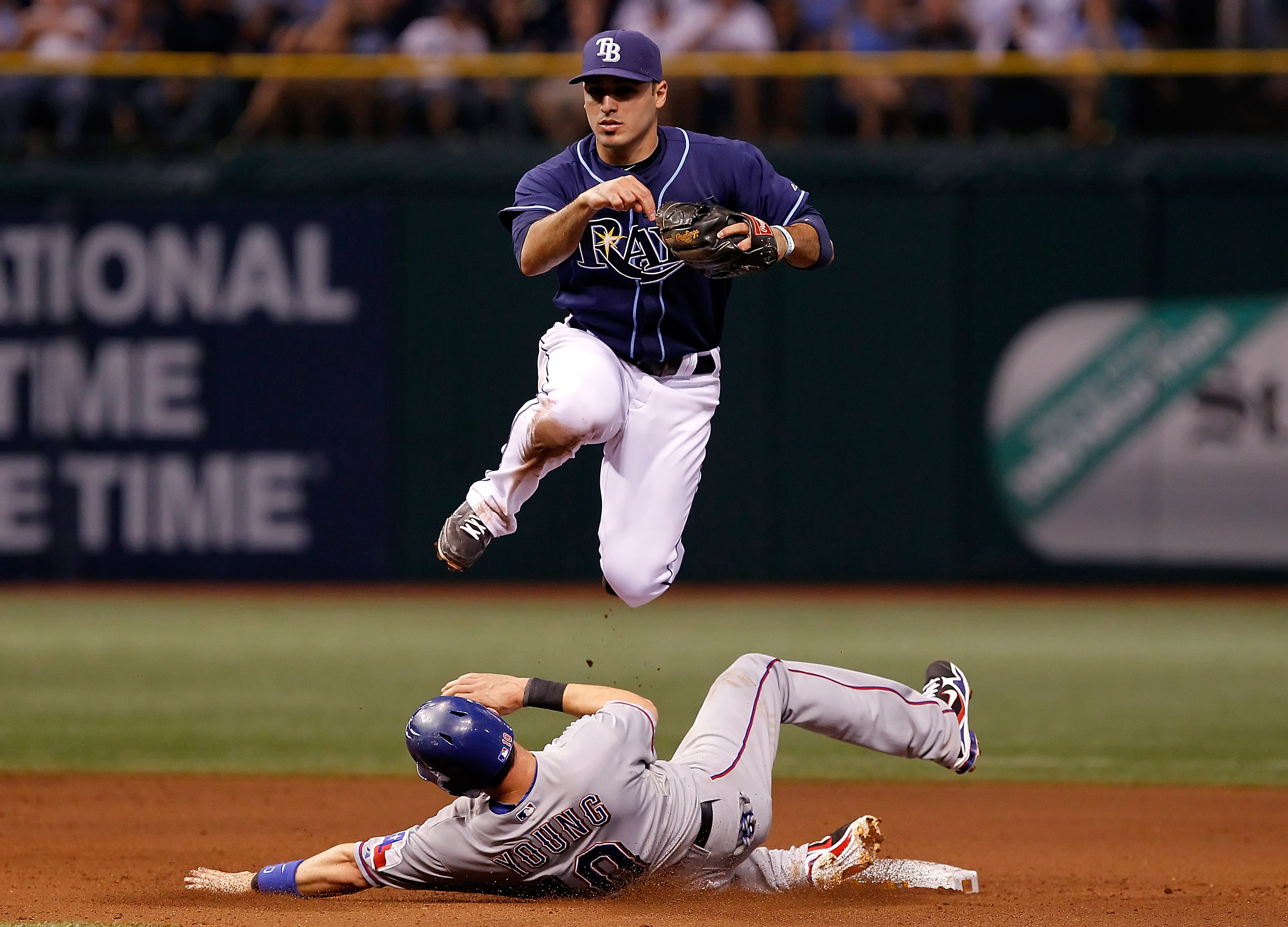 ST. PETERSBURG, FL - OCTOBER 12:  Infielder Sean Rodriguez #1 of the Tampa Bay Rays turns a double play as Michael Young #10 of the Texas Rangers tries to break it up during Game 5 of the ALDS at Tropicana Field on October 12, 2010 in St. Petersburg, Flor