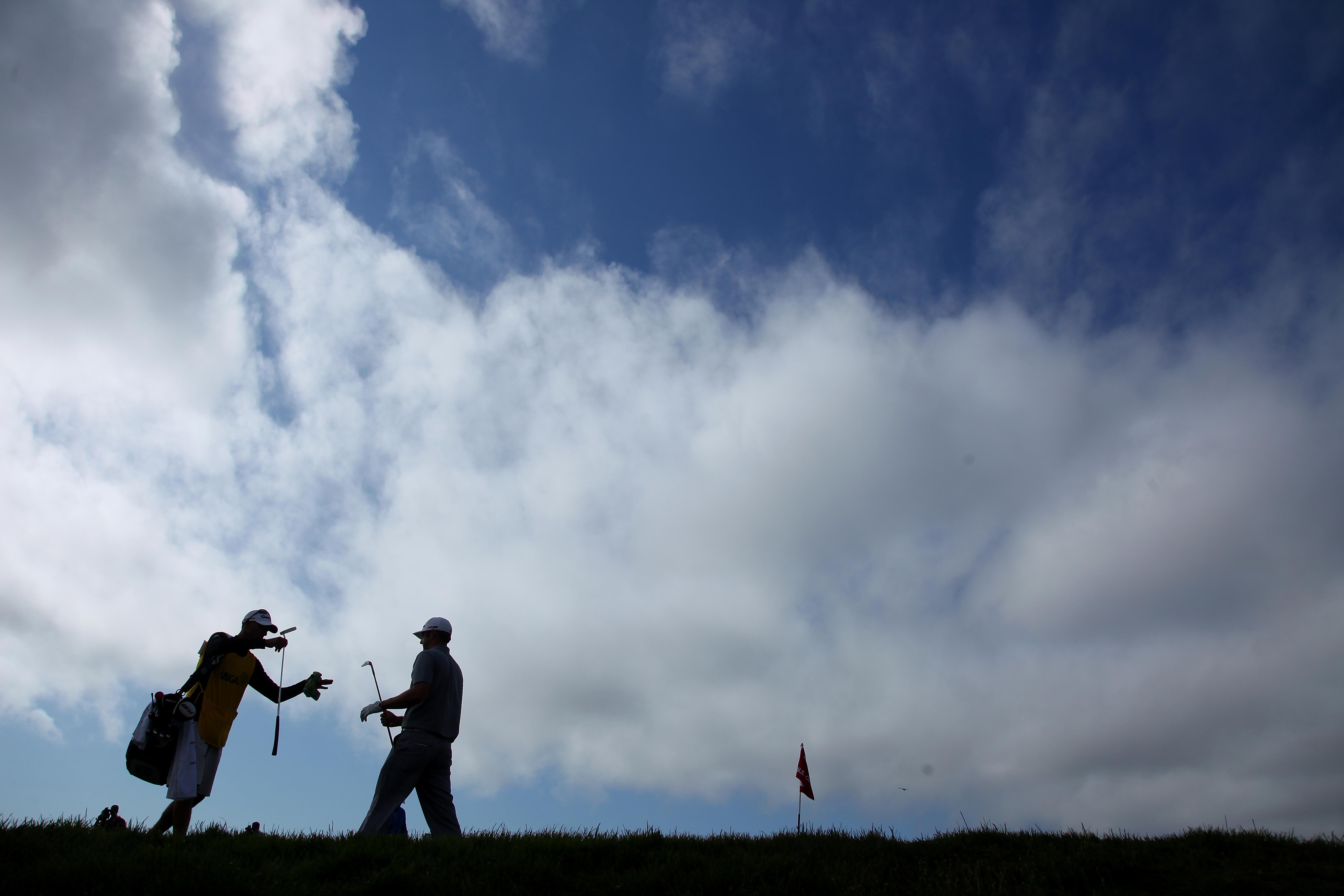 PEBBLE BEACH, CA - JUNE 19:  Dustin Johnson grabs his putter from his caddie Bobby Brown on the eigth hole during the third round of the 110th U.S. Open at Pebble Beach Golf Links on June 19, 2010 in Pebble Beach, California.  (Photo by Donald Miralle/Get