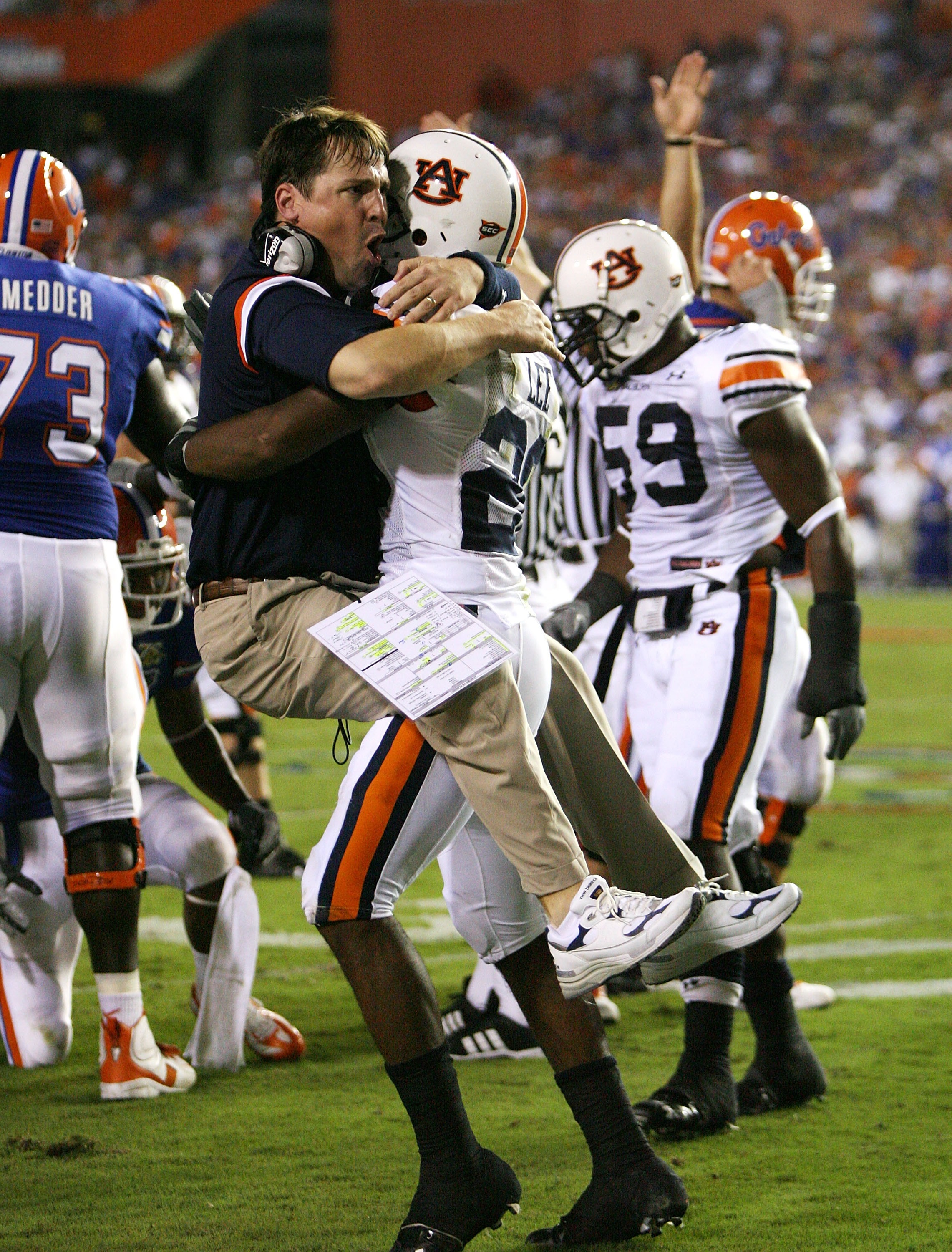 GAINESVILLE, FL - SEPTEMBER 29:  Defensive coordinator Will Muschamp of the Auburn Tigers jumps into the arms of defensive back Patrick Lee #20 after Lee helped cause a fumble late in the first half against the Florida Gators at Ben Hill Griffin Stadium S