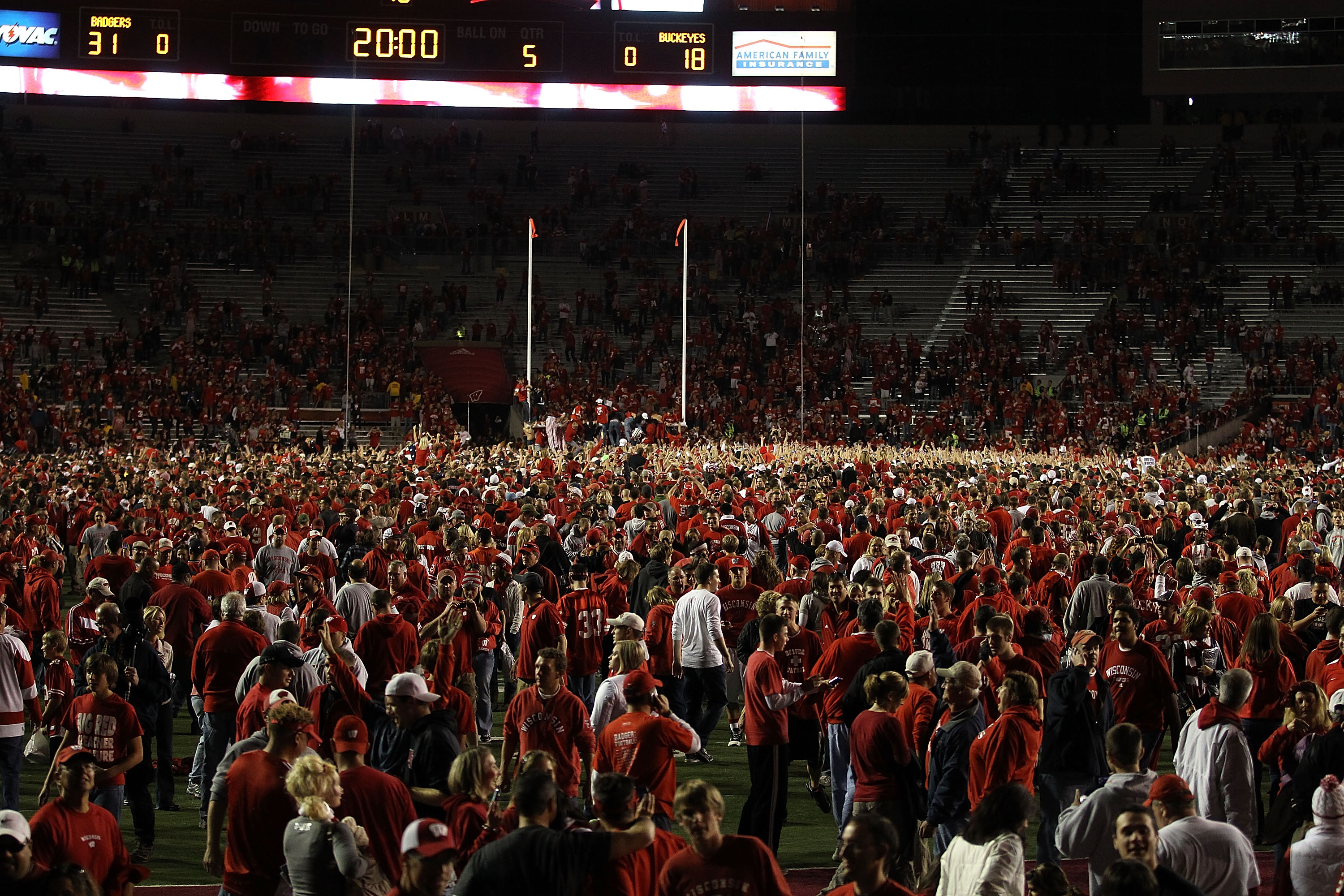 MADISON, WI - OCTOBER 16: Fans of the Wisconsin Badgers poor on to the field following a win against the Ohio State Buckeyes at Camp Randall Stadium on October 16, 2010 in Madison, Wisconsin. Wisconsin defeated Ohio State 31-18. (Photo by Jonathan Daniel/