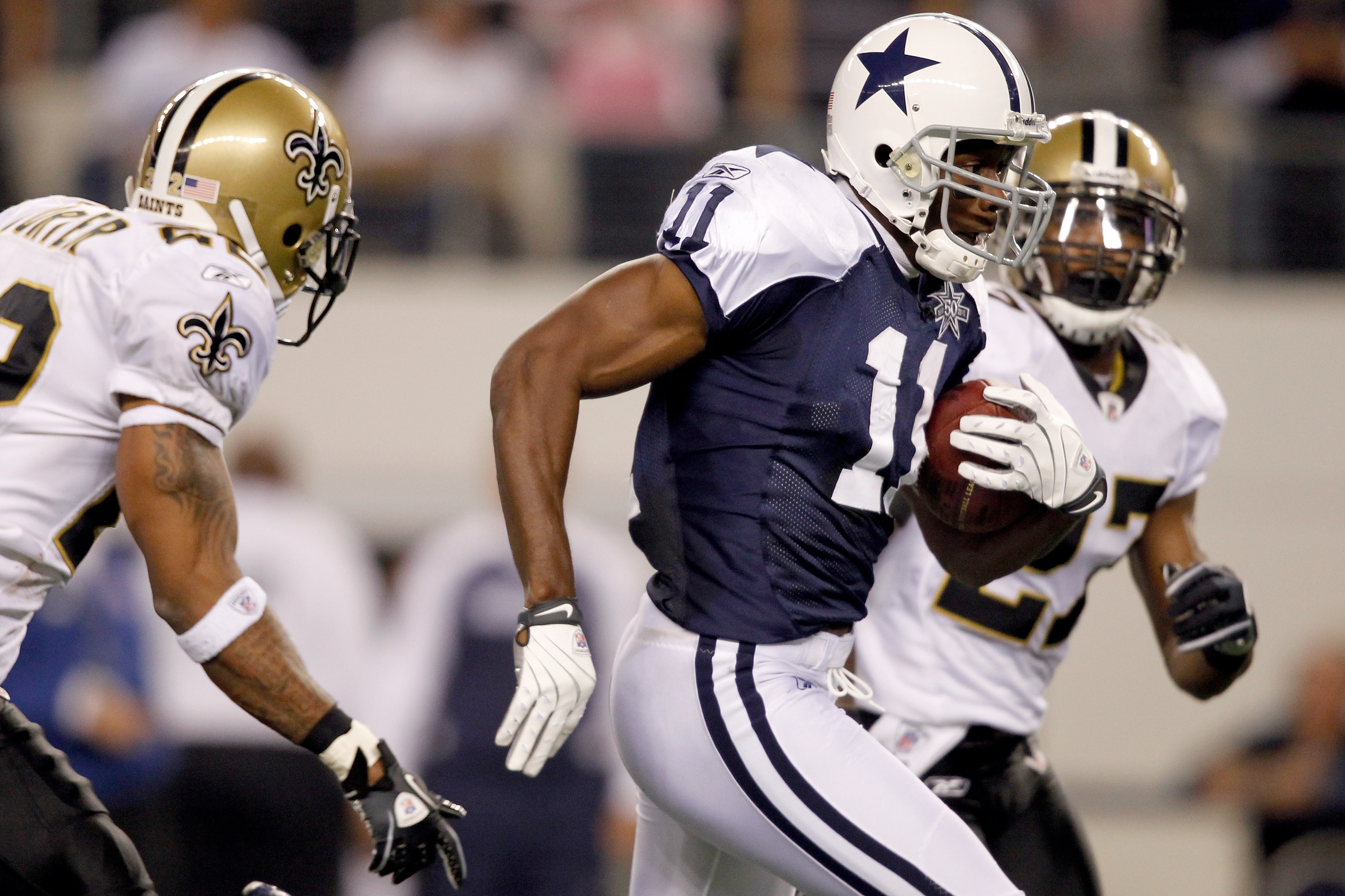 ARLINGTON, TX - NOVEMBER 25: Roy Williams #11 of the Dallas Cowboys carries the ball after making a reception  while being pursued by Malcolm Jenkins #27  of the New Orleans Saints at Cowboys Stadium on November 25, 2010 in Arlington, Texas. Jenkins would