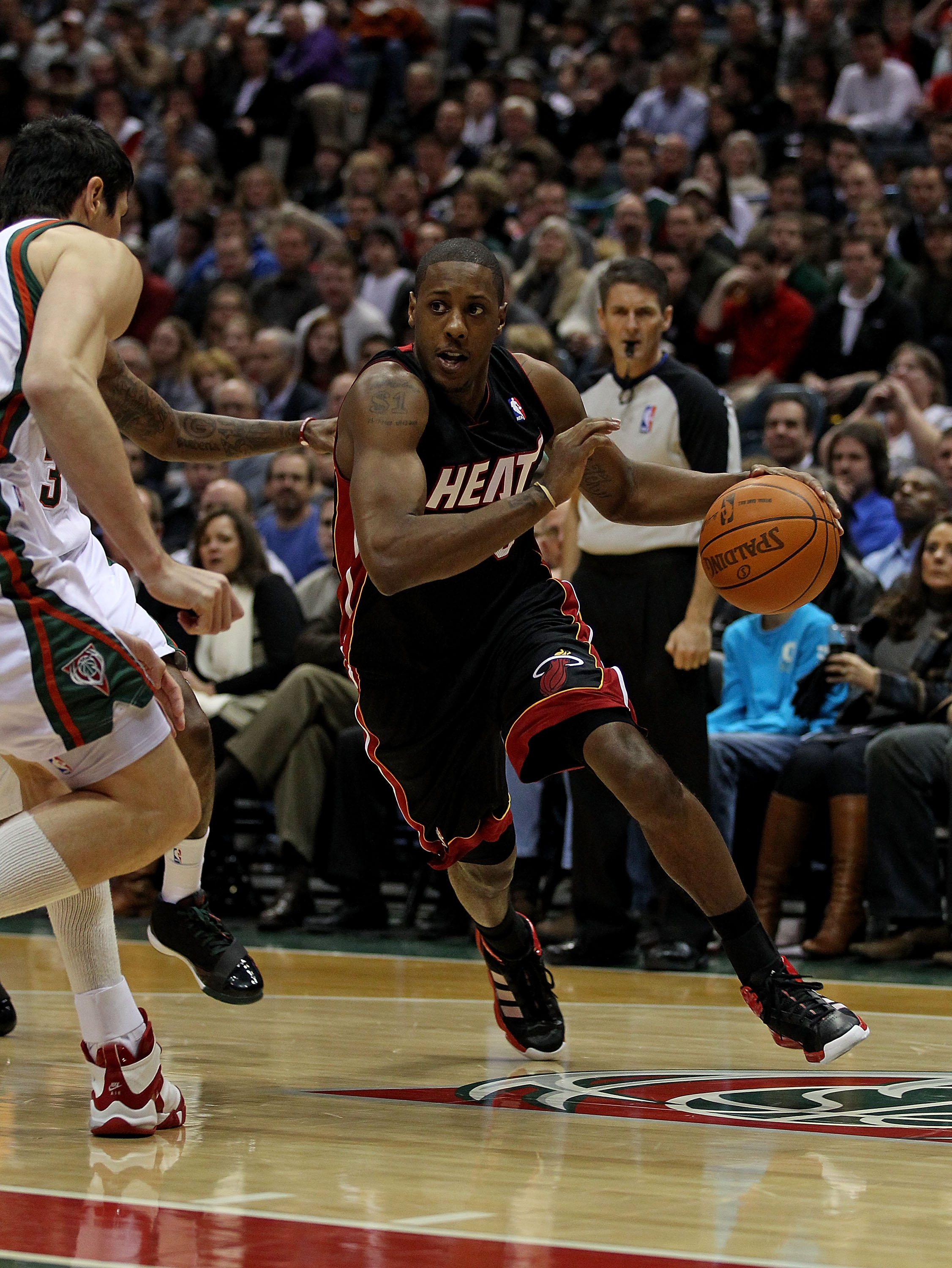 MILWAUKEE, WI - DECEMBER 06: Mario Chalmers #15 of the Miami Heat drives towards Ersan Ilyasova #7 of the Milwaukee Bucks at the Bradley Center on December 6, 2010 in Milwaukee, Wisconsin. The Heat defeated the Bucks 88-78. NOTE TO USER: User expressly ac