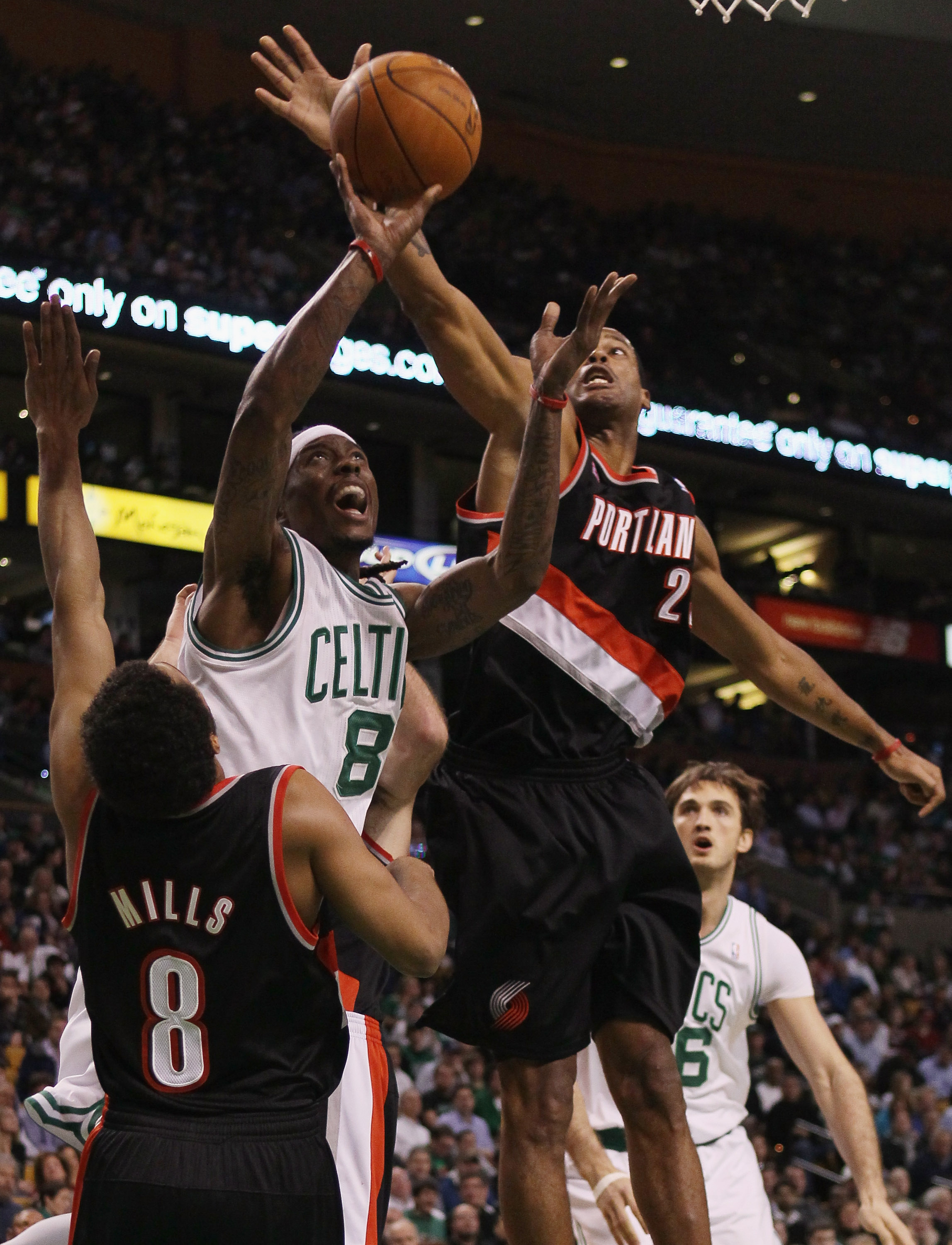 BOSTON - DECEMBER 01:  Marquis Daniels #8 of the Boston Celtics tries to take a shot as Marcus Camby #23 and Patrick Mills #8 of the Portland Trailblazers defend on December 1, 2010 at the TD Garden in Boston, Massachusetts.  NOTE TO USER: User expressly