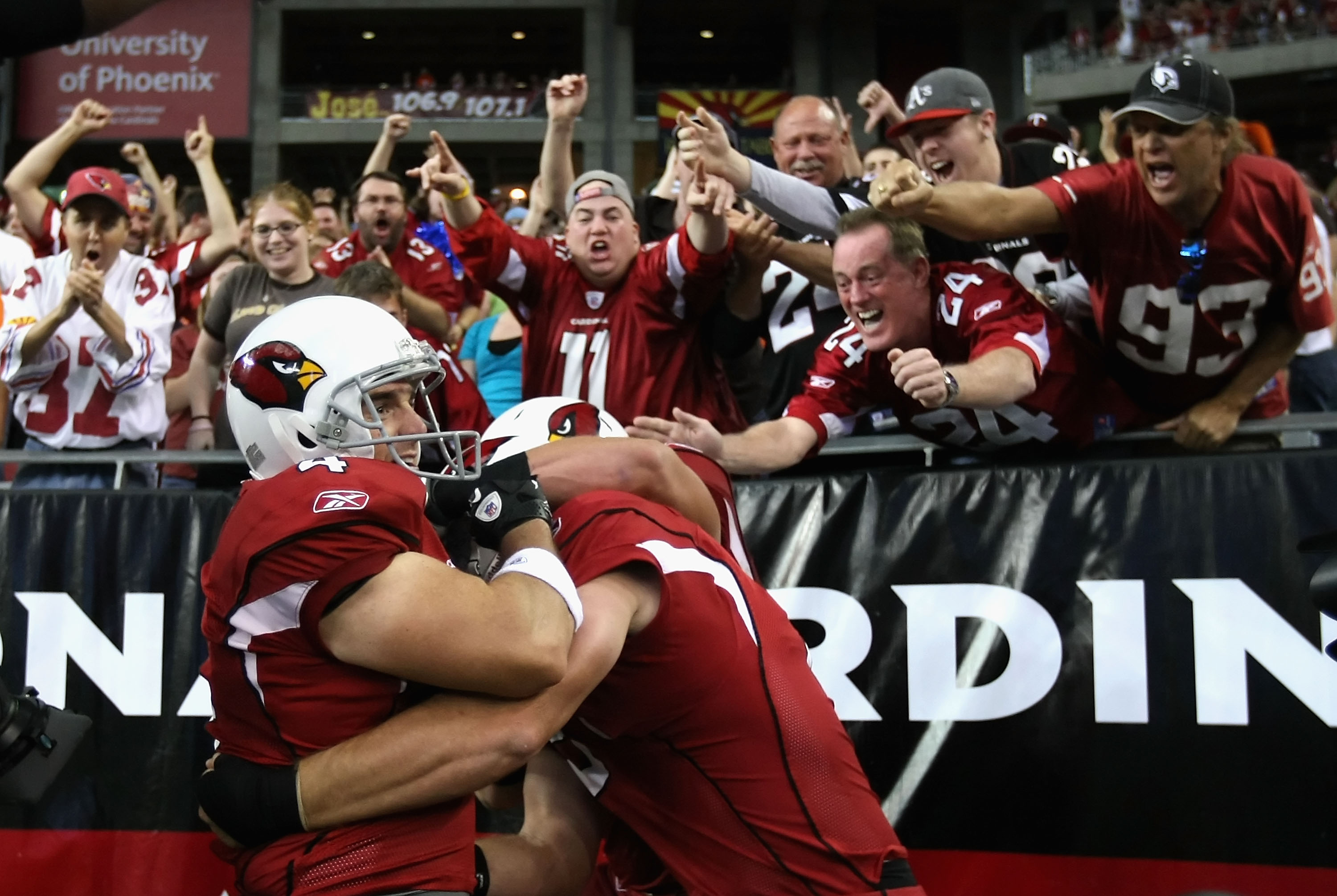 GLENDALE, AZ - DECEMBER 12:  Kicker Jay Feely #4 of the Arizona Cardinals celebrates with teamamtes and fans after scoring on a 5 yard rushing touchdown against the Denver Broncos during the second quarter of the NFL game at the University of Phoenix Stad