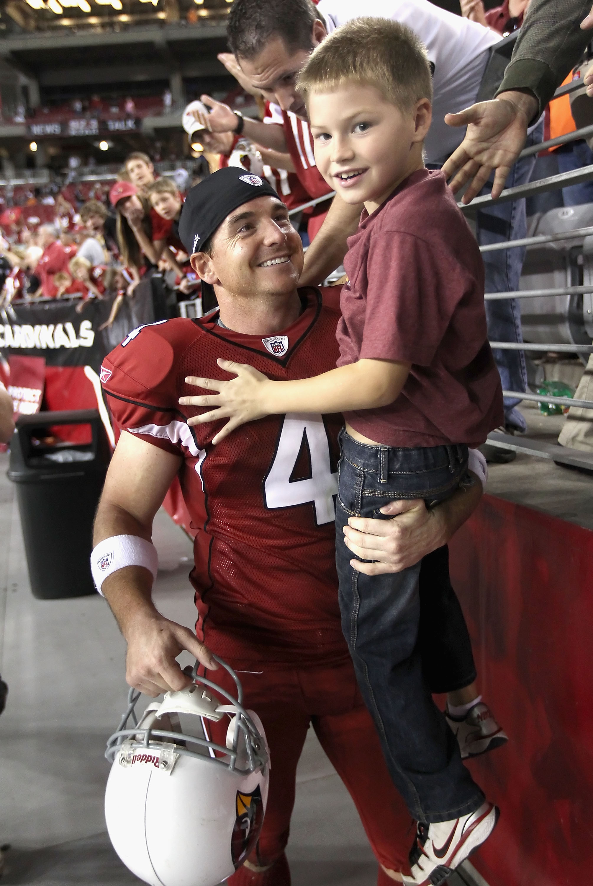 GLENDALE, AZ - DECEMBER 12:  Kicker Jay Feely #4 of the Arizona Cardinals lifts his son Jace out of the crowd following the NFL game against the Denver Broncos at the University of Phoenix Stadium on December 12, 2010 in Glendale, Arizona.  The Cardinals