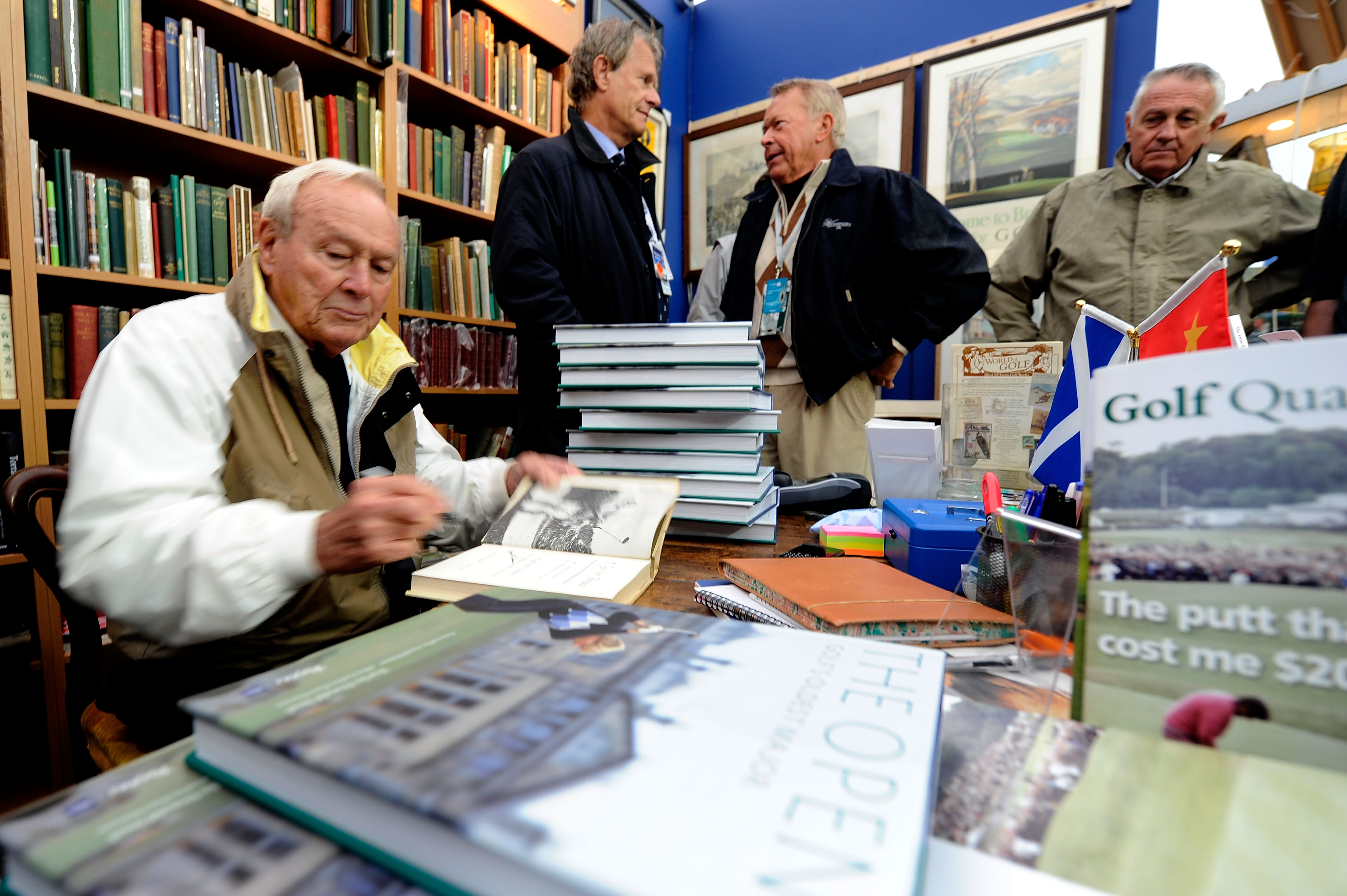 ST ANDREWS, SCOTLAND - JULY 14:  Arnold Palmer autographs books for fans at the merchandise pavilion during practice for the 139th Open Championship on the Old Course, St Andrews on July 14, 2010 in St Andrews, Scotland.  (Photo by Stuart Franklin/Getty I