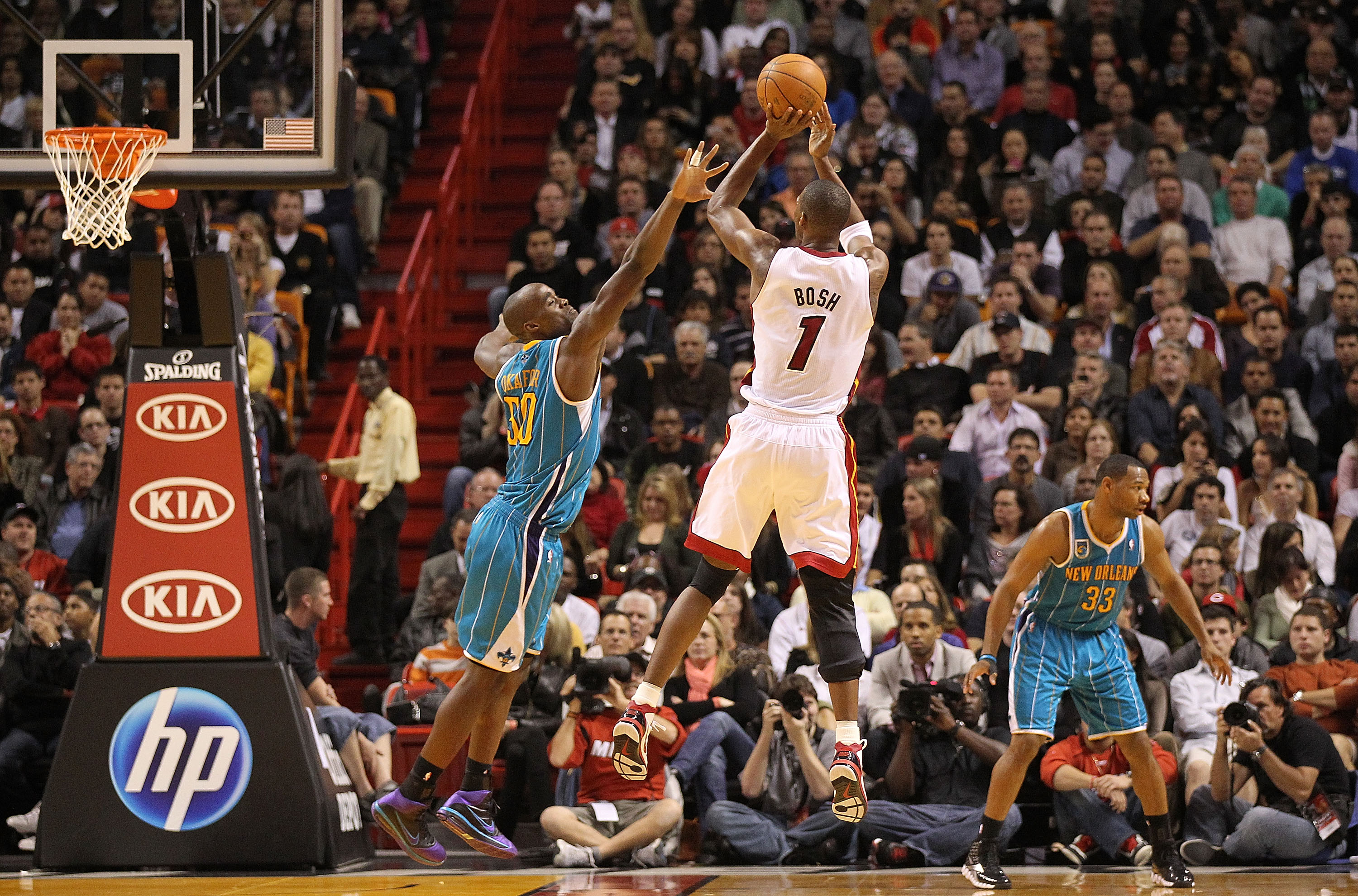 MIAMI, FL - DECEMBER 13:  Chris Bosh #1 of the Miami Heat shoots over Emeka Okafor #50 of the New Orleans Hornets during a game at American Airlines Arena on December 13, 2010 in Miami, Florida. NOTE TO USER: User expressly acknowledges and agrees that, b