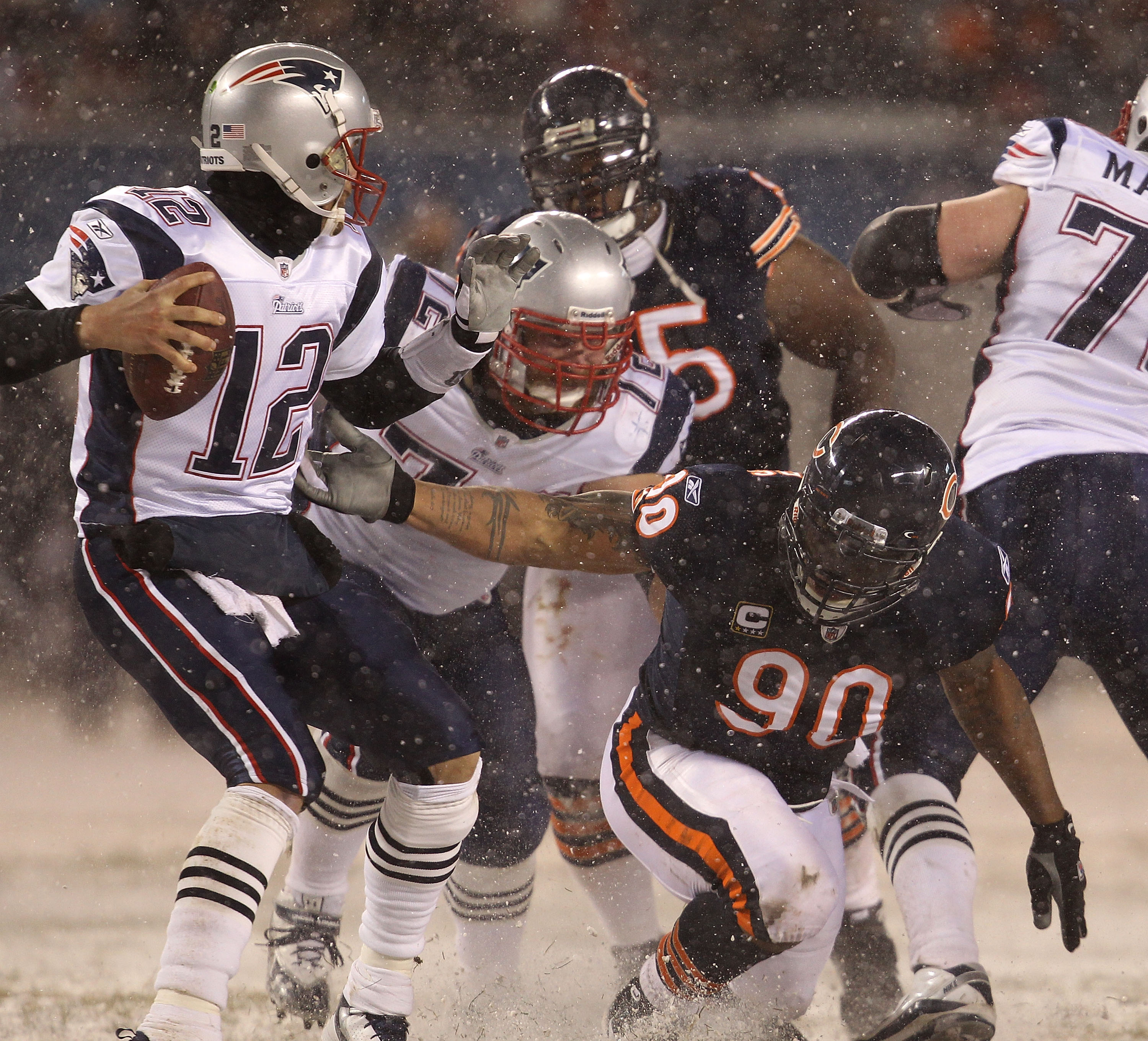CHICAGO - DECEMBER 12: Julius Peppers #90 of the Chicago Bears slips as he grabs Tom Brady #12 of the New England Patriots at Soldier Field on December 12, 2010 in Chicago, Illinois. The Patriots defeated the Bears 36-7. (Photo by Jonathan Daniel/Getty Im