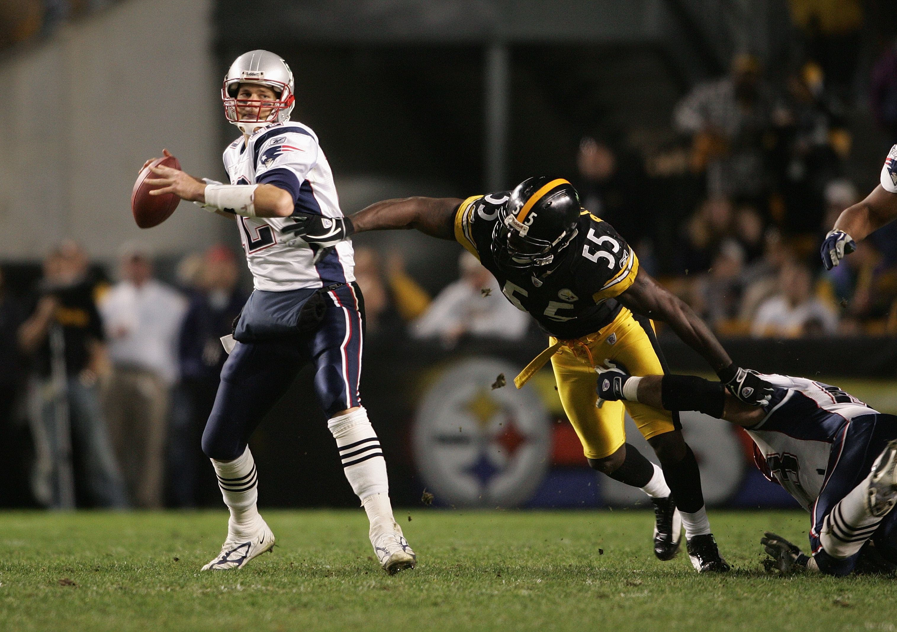 PITTSBURGH - OCTOBER 31:  Quarterback Tom Brady #12 of the New England Patriots attempts to pass the ball before being sacked by outside linebacker Joey Porter #55 of the Pittsburgh Steelers during the game at Heinz Field on October 31, 2004 in Pittsburgh