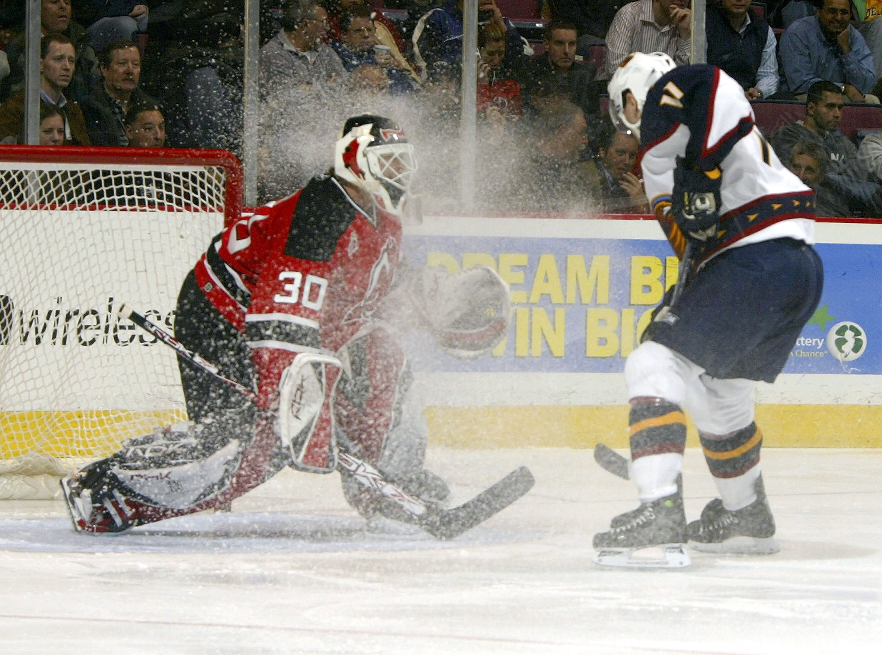 EAST RUTHERFORD, NJ - DECEMBER 19:  Goaltender Martin Broduer #30 of the New Jersey Devils  has ice kicked up into his face by J.P. Vigier #11 of the Atlanta Thrashers on December 19, 2006 at the Continental Airlines Arena in East Rutherford, New Jersey.