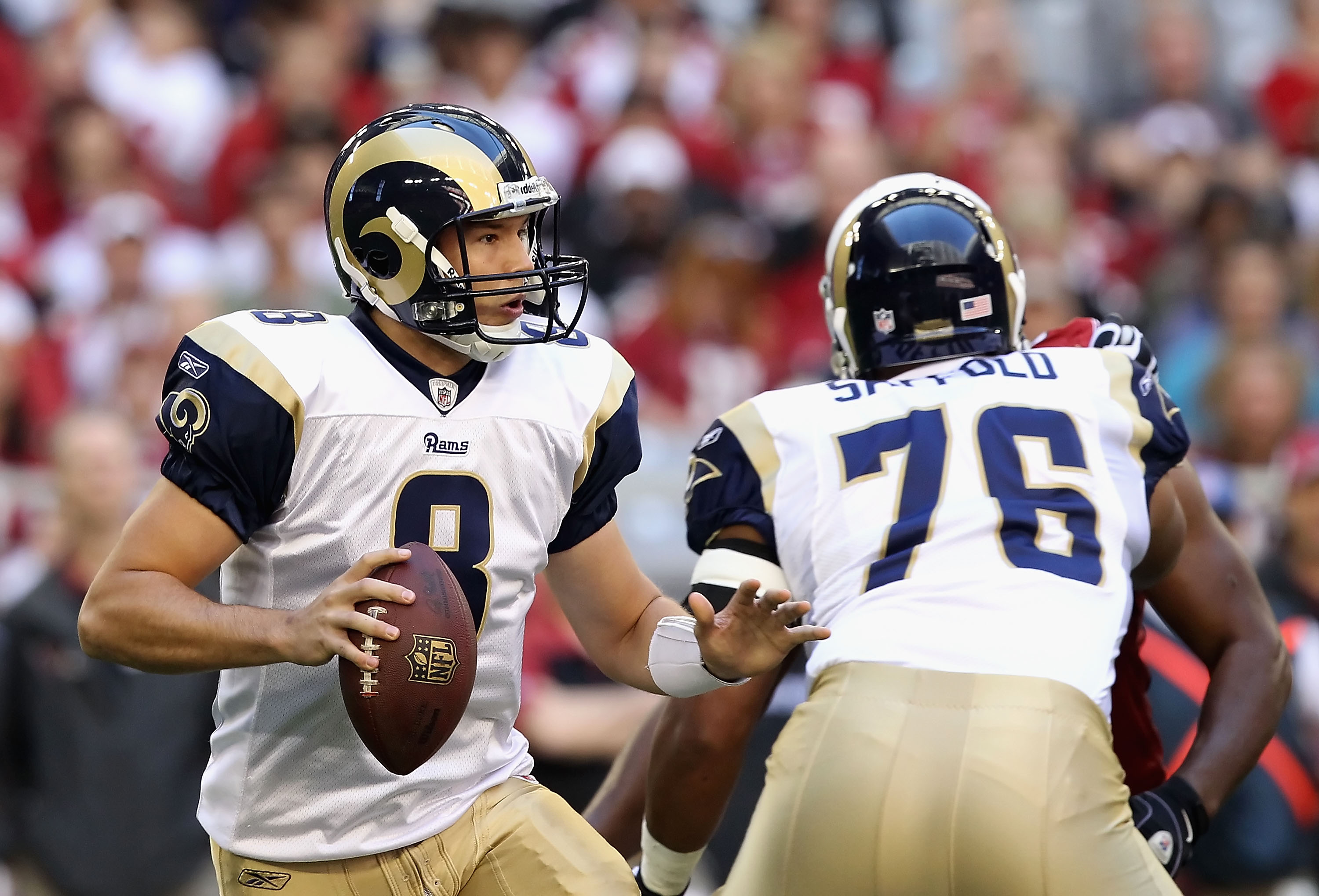 GLENDALE, AZ - DECEMBER 05:  Quarterback Sam Bradford #8 of the St. Louis Rams scrambles to pass the football during the NFL game against the Arizona Cardinals at the University of Phoenix Stadium on December 5, 2010 in Glendale, Arizona. The Rams defeate
