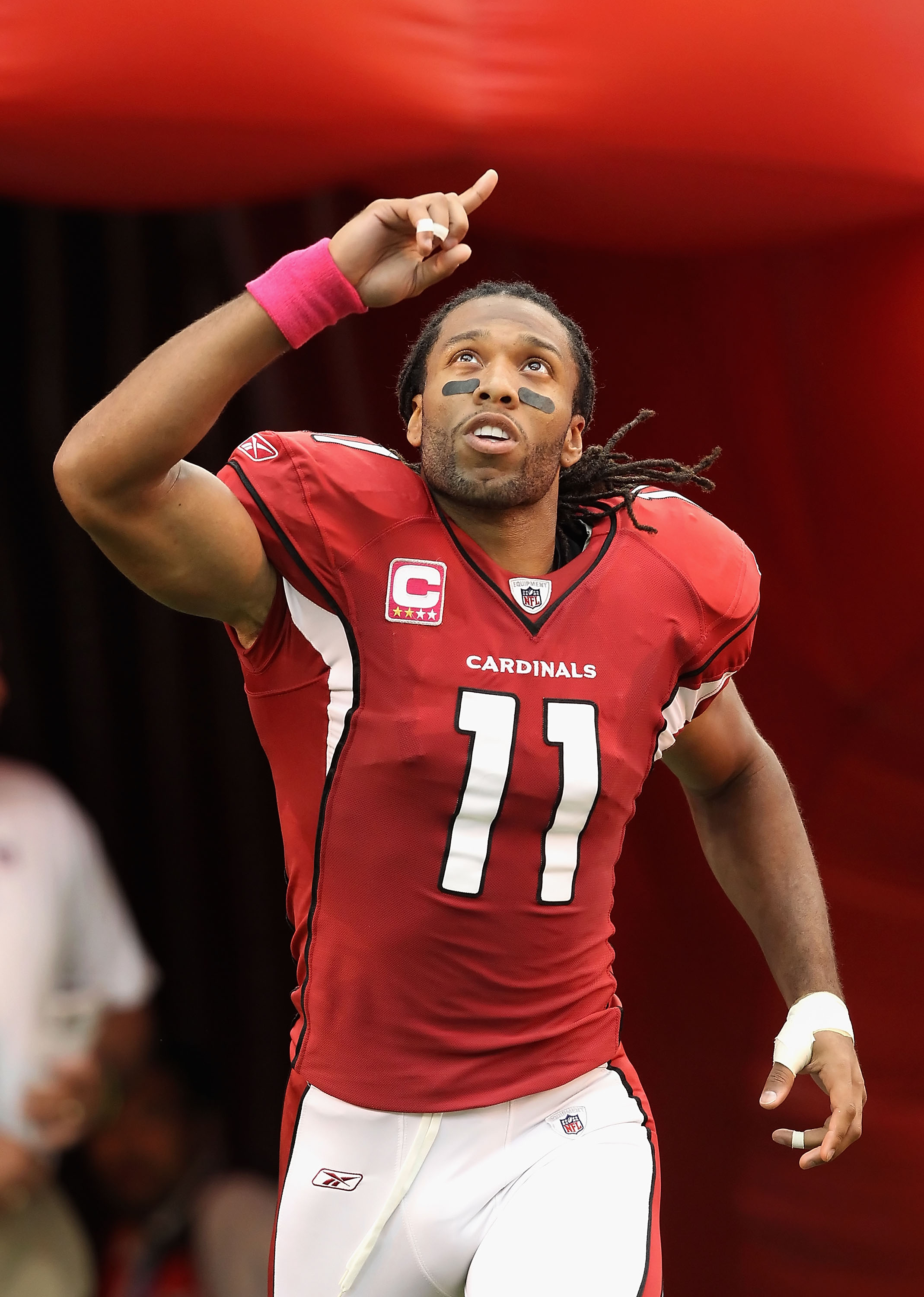 GLENDALE, AZ - OCTOBER 10:  Wide receiver Larry Fitzgerald #11 of the Arizona Cardinals runs onto the field during introductions to the NFL game against the New Orleans Saints at the University of Phoenix Stadium on October 10, 2010 in Glendale, Arizona.