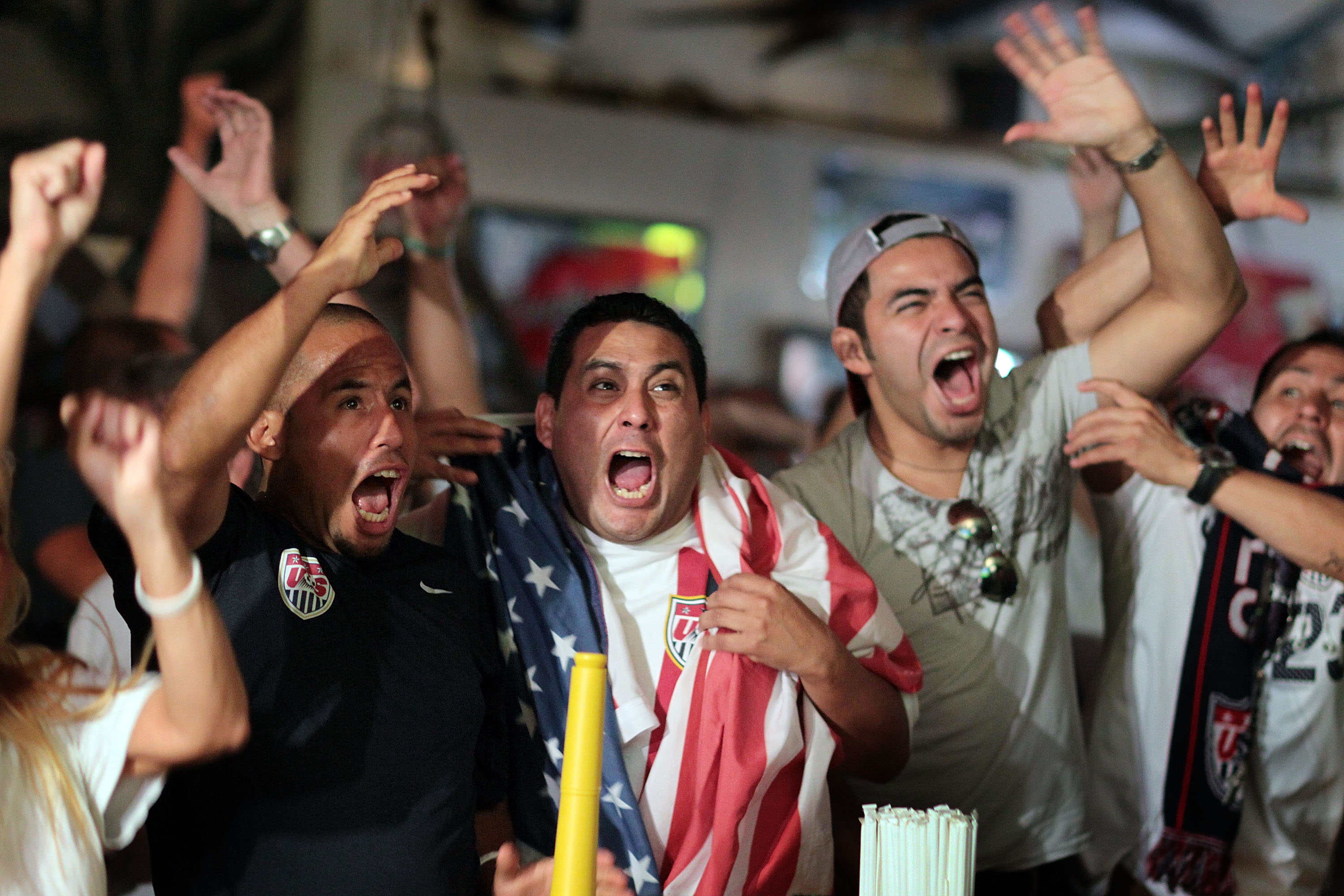 MIAMI - JUNE 23:  Freddy Hurtado (L) and Wilfredo Hurtado (C) and others celebrate the winning goal for the USA soccer team while watching the 2010 FIFA World Cup South Africa Group C match between USA and Algeria on television at Churchill's pub on June