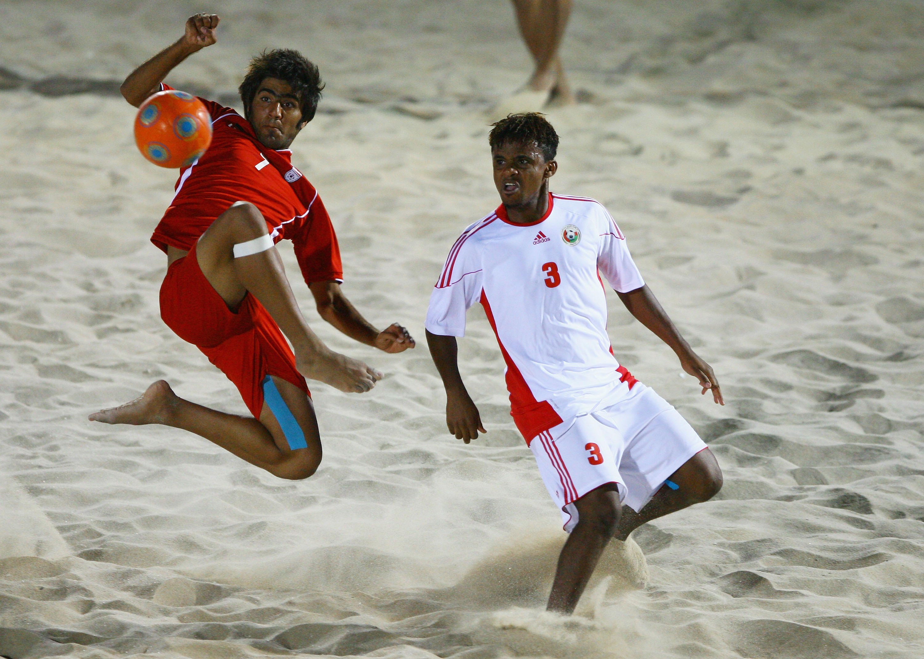 MUSCAT, OMAN - DECEMBER 15:   Mehran Morshedizadeh of Iran fights for the ball with Jalal Al Sinani of Oman in the Beach Soccer Semi Final between Oman and Iran at Al-Musannah Sports City during day eight of the 2nd Asian Beach Games Muscat 2010 on Decemb