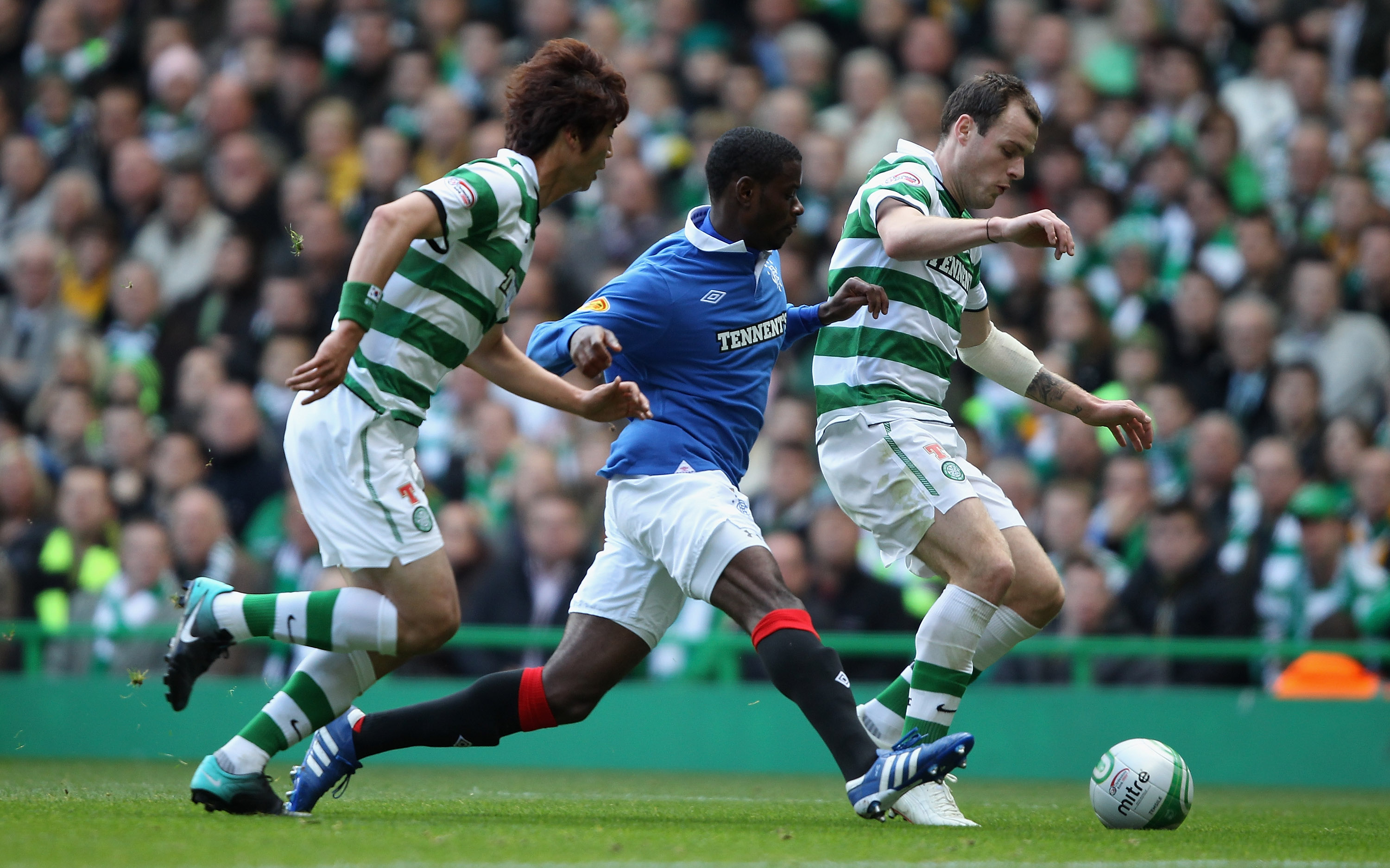 GLASGOW, SCOTLAND - OCTOBER 24:  Anthony Stokes of Celtic attempts to move away from Maurice Edu of Rangers during the Clydesdale Bank Premier League match between Celtic and Rangers at Celtic Park on October 24, 2010 in Glasgow, Scotland.  (Photo by Cliv