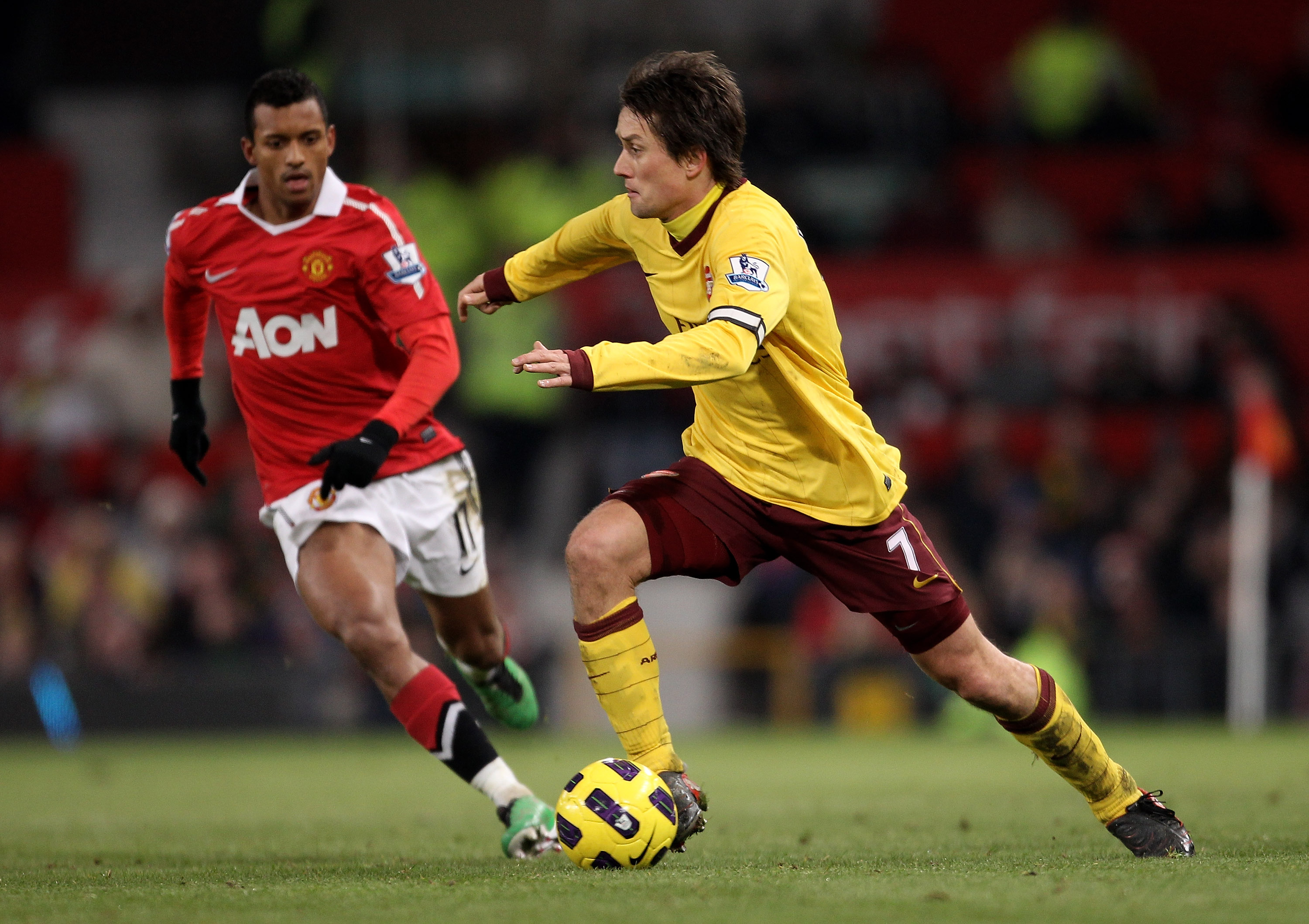 MANCHESTER, ENGLAND - DECEMBER 13:  Tomas Rosicky of Arsenal is pursued by Nani of Manchester United during the Barclays Premier League match between Manchester United and Arsenal at Old Trafford on December 13, 2010 in Manchester, England.  (Photo by Ale