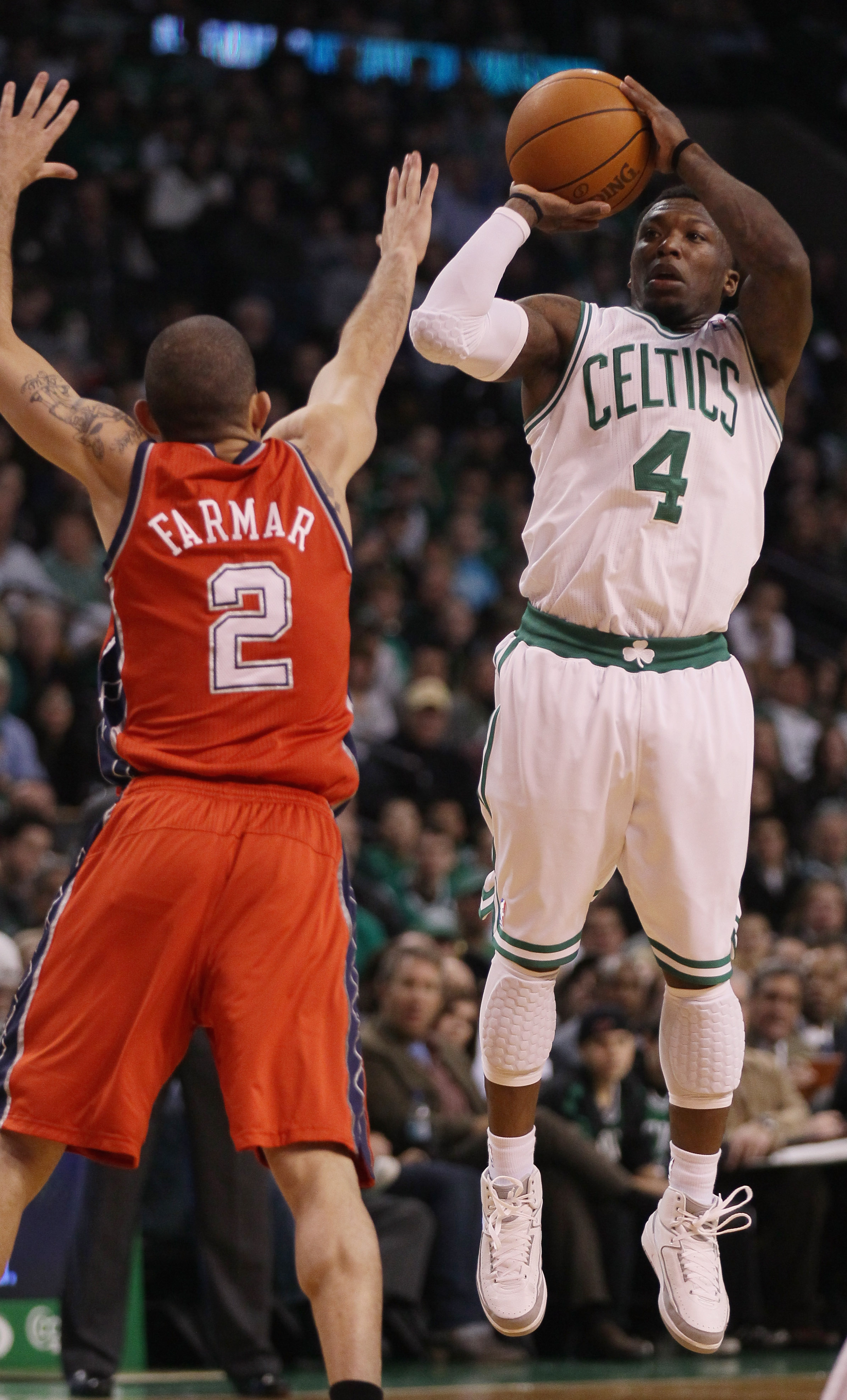 BOSTON - NOVEMBER 24:  Nate Robinson #4 of the Boston Celtics takes a shot as Jordan Farmar #2 of the New Jersey Nets defends on November 24, 2010 at the TD Garden in Boston, Massachusetts. NOTE TO USER: User expressly acknowledges and agrees that, by dow
