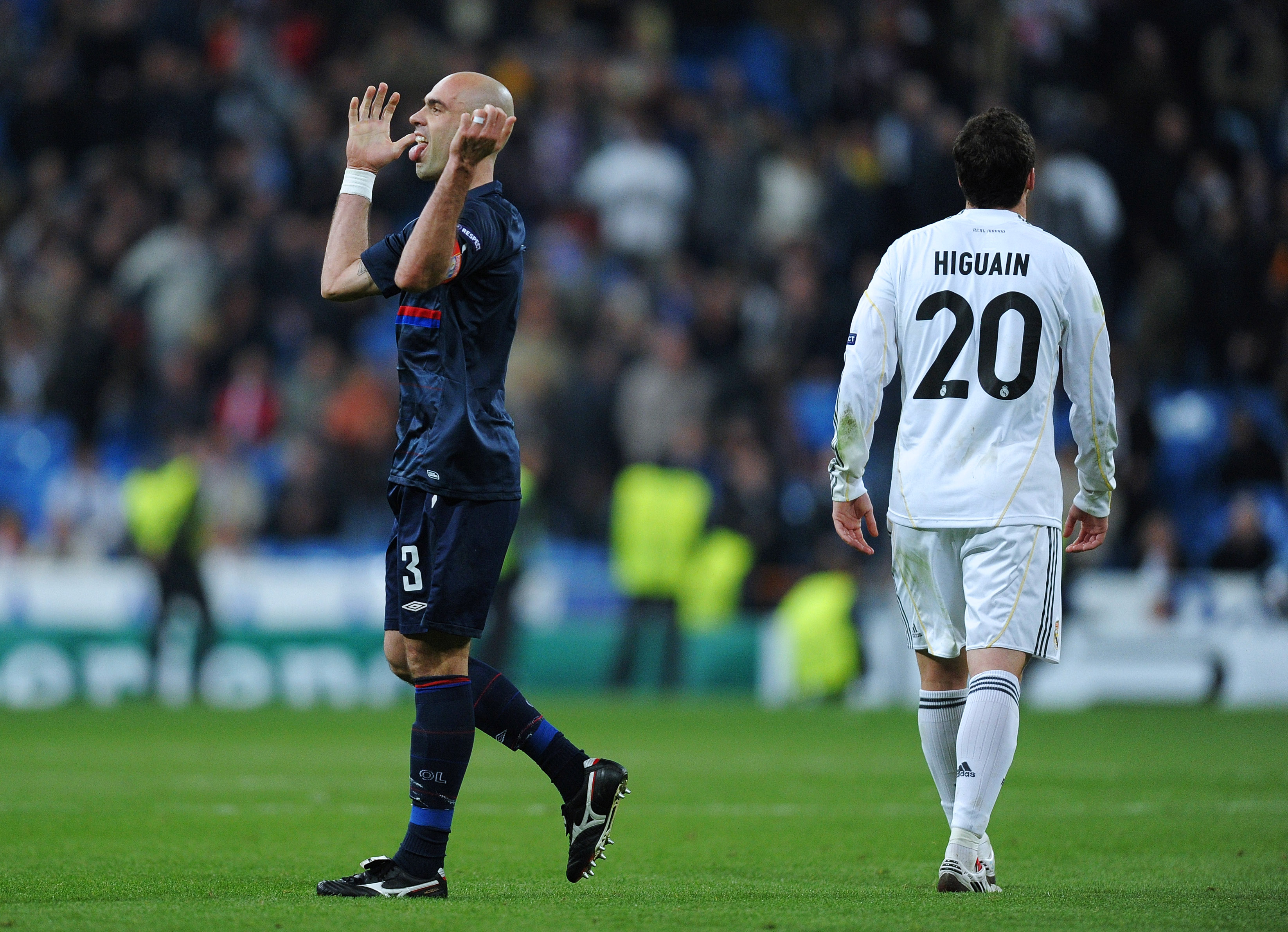 MADRID, SPAIN - MARCH 10:  Cris (L) captain of Lyon celebrates as Gonzalo Higuain of Real Madrid trudges off the pitch during the UEFA Champions League round of 16 second leg match between Real Madrid and Lyon at the Estadio Santiago Bernabeu on March 10,