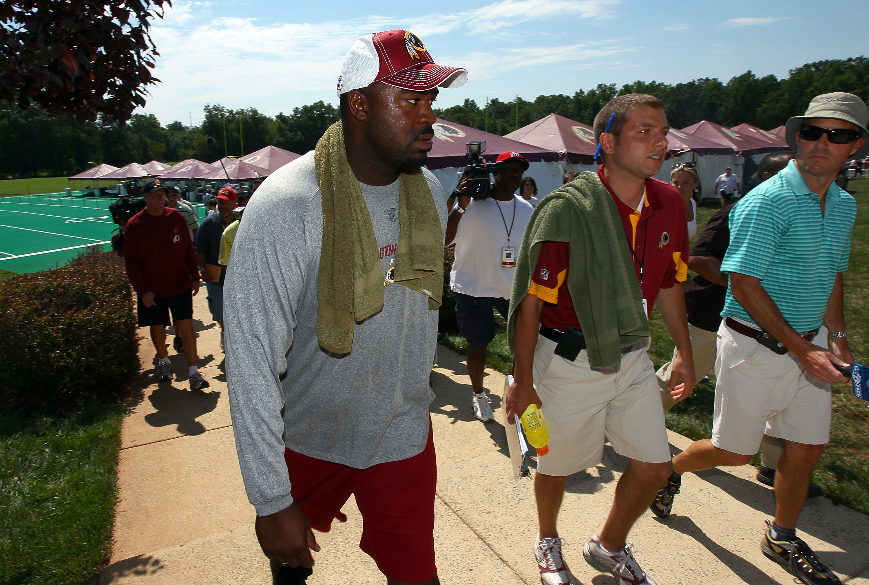 ASHBURN, VA - JULY 30:  Defensive lineman Albert Haynesworth #92 (L) returns to the locker room following a workout session with Redskins defensive coordinator Jim Haslett (2nd L) on the second day of training camp July 30, 2010 in Ashburn, Virginia. Hayn