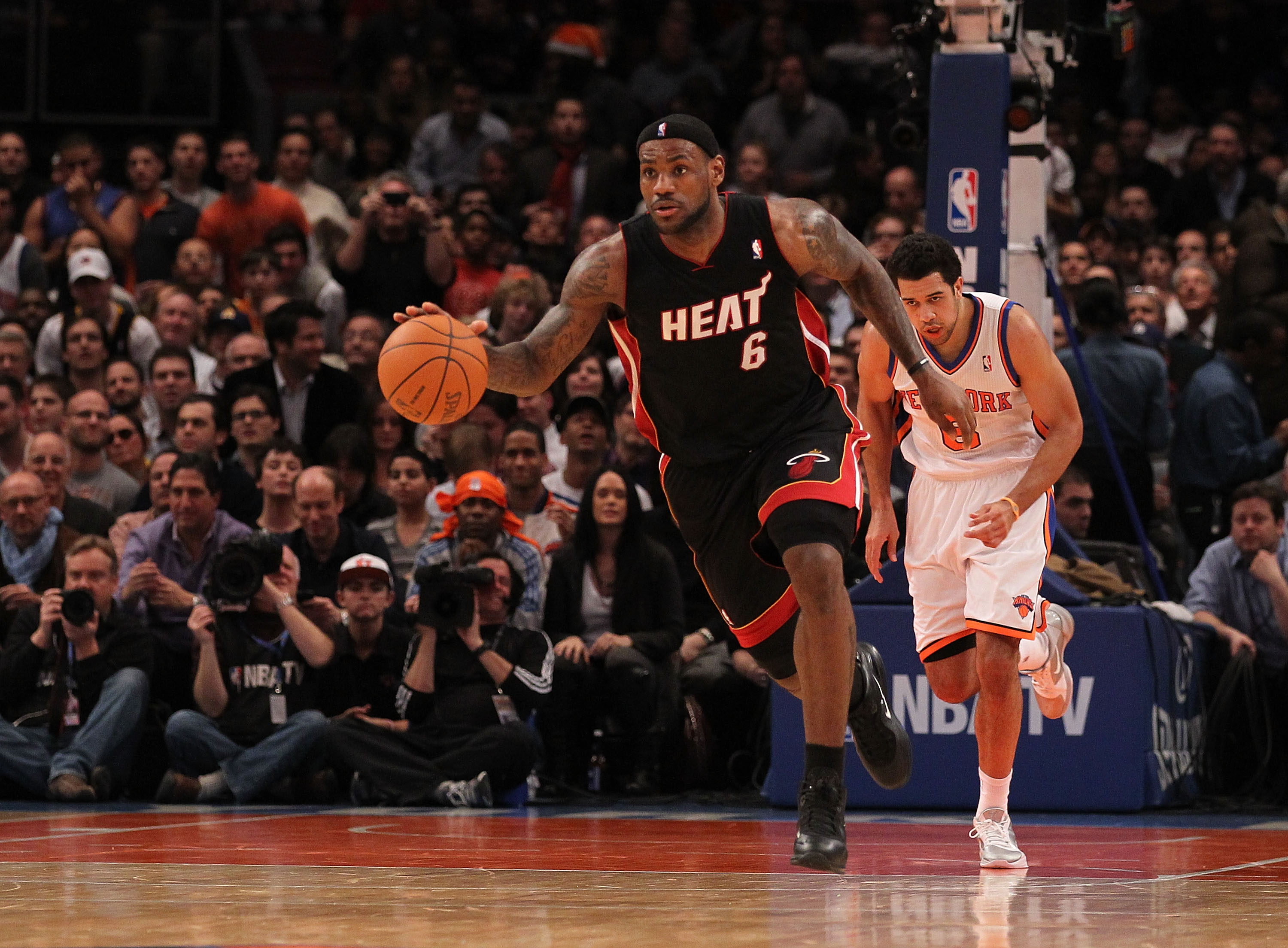 NEW YORK - DECEMBER 17:  LeBron James #6 of the Miami Heat dribbles the ball as Landry Fields #6 of the New York Knicks  gives chase at Madison Square Garden on December 17, 2010 in New York City. NOTE TO USER: User expressly acknowledges and agrees that,