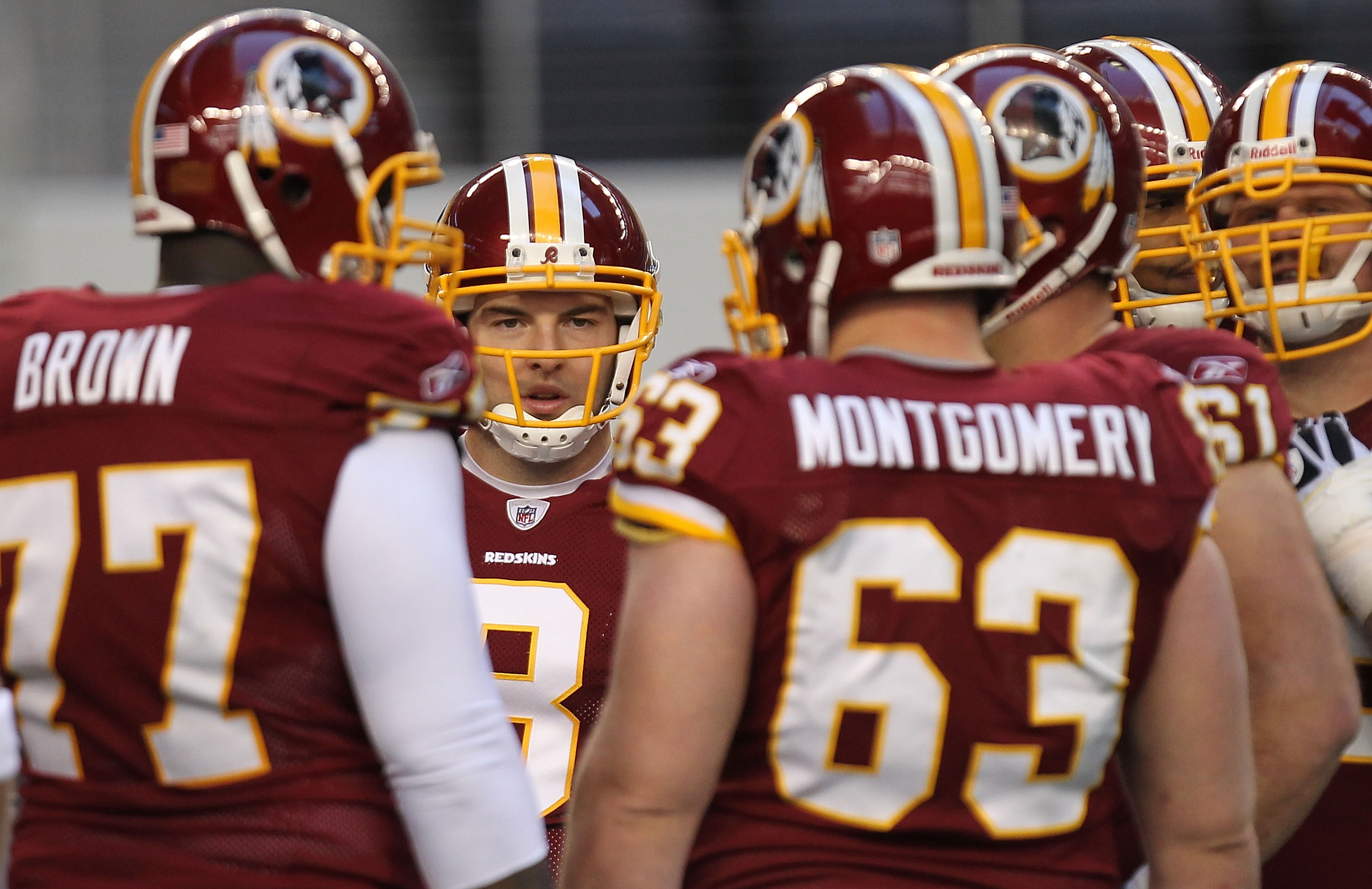 ARLINGTON, TX - DECEMBER 19:  Quarterback Rex Grossman #8 of the Washington Redskins huddles the offense against the Dallas Cowboys in the first quarter at Cowboys Stadium on December 19, 2010 in Arlington, Texas.  (Photo by Ronald Martinez/Getty Images)