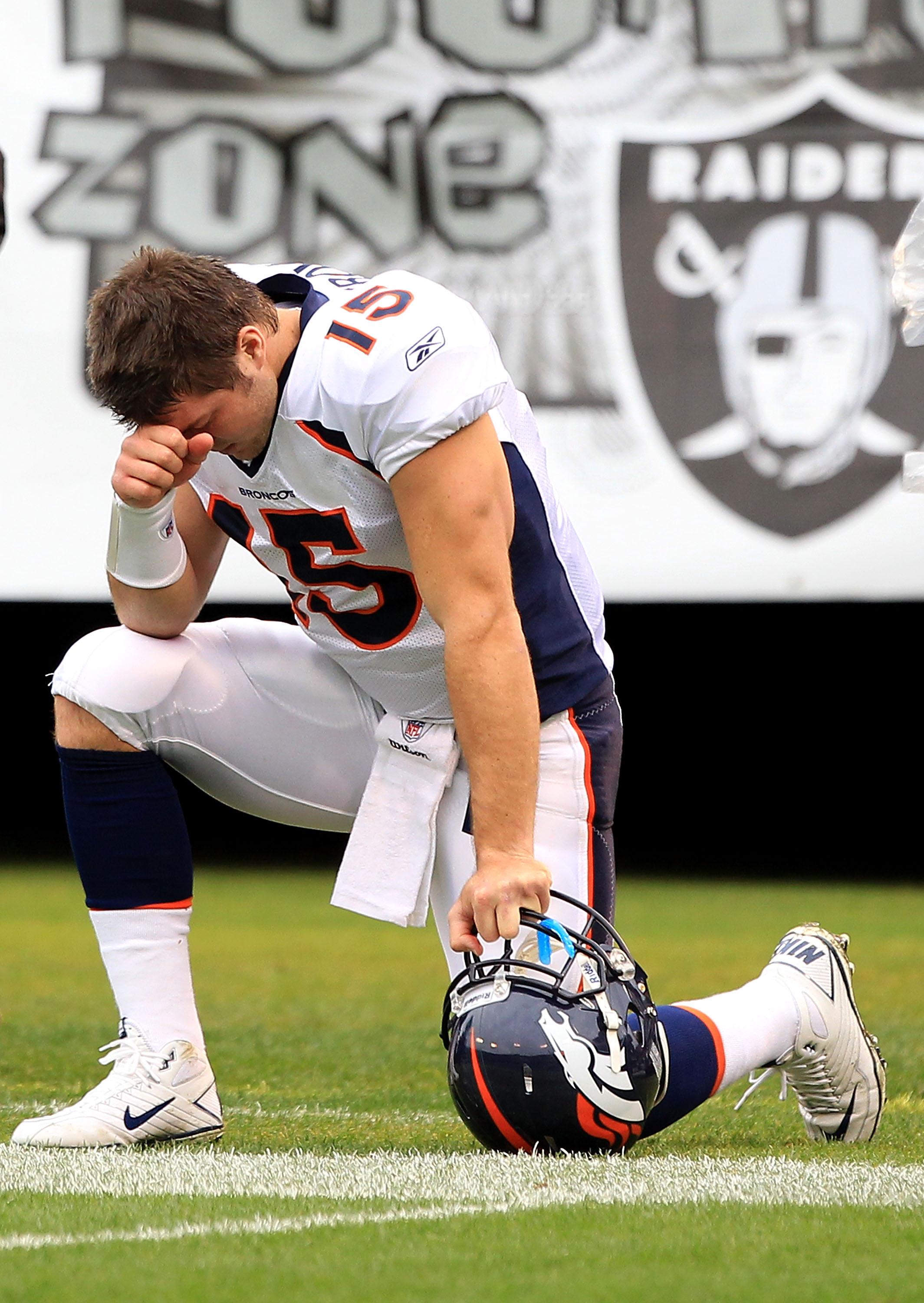 OAKLAND, CA - DECEMBER 19:  Tim Tebow #15 of the Denver Broncos kneels on the ground before their game against the Oakland Raiders at Oakland-Alameda County Coliseum on December 19, 2010 in Oakland, California.  (Photo by Ezra Shaw/Getty Images)
