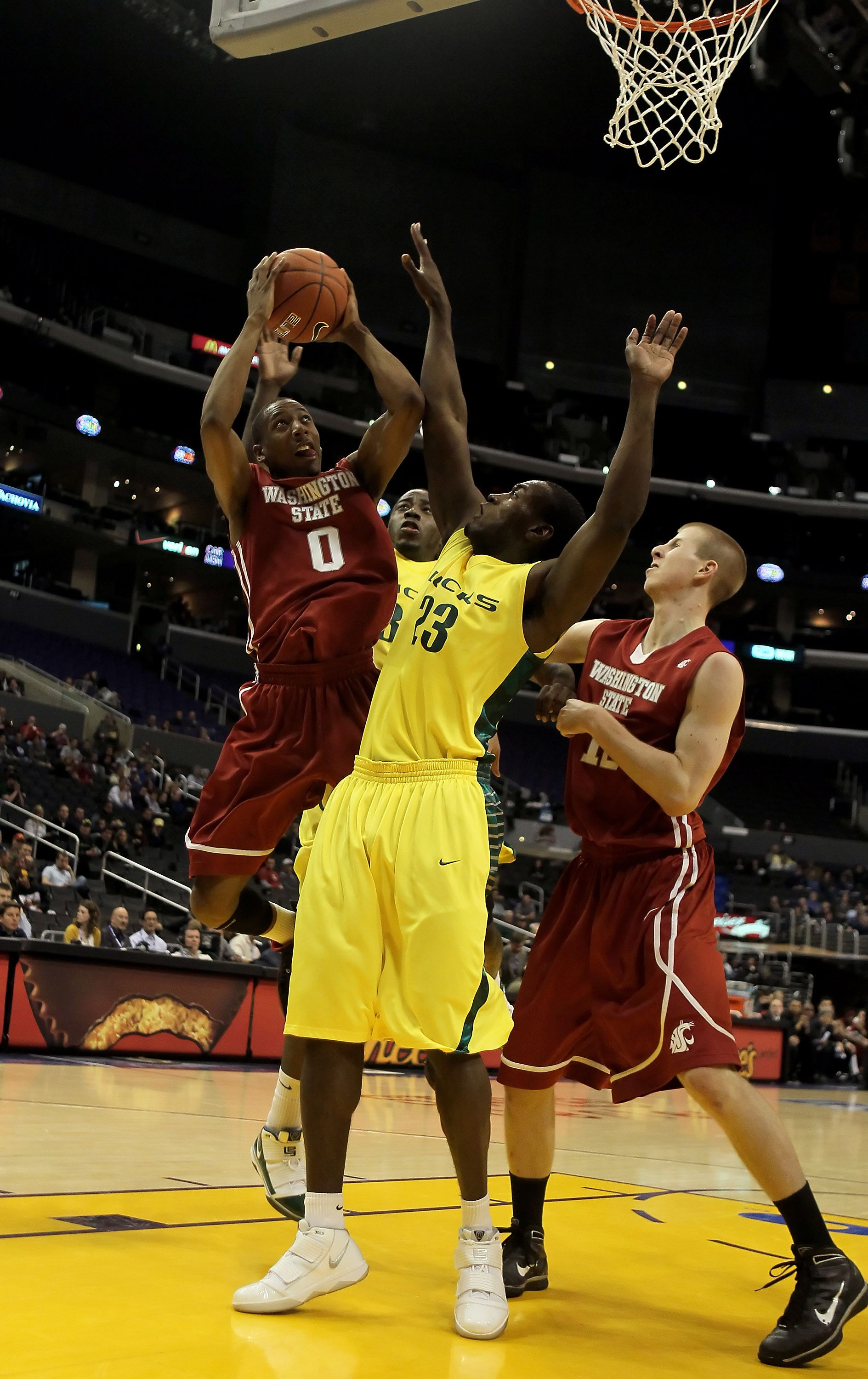 LOS ANGELES, CA - MARCH 10:  Marcus Capers #0 of the Washington State Cougars drives to the basket while being defended by DeAngelo Casto #23 of the Oregon Ducks in the half during the first round of the Pac-10 Basketball Tournament at Staples Center on M