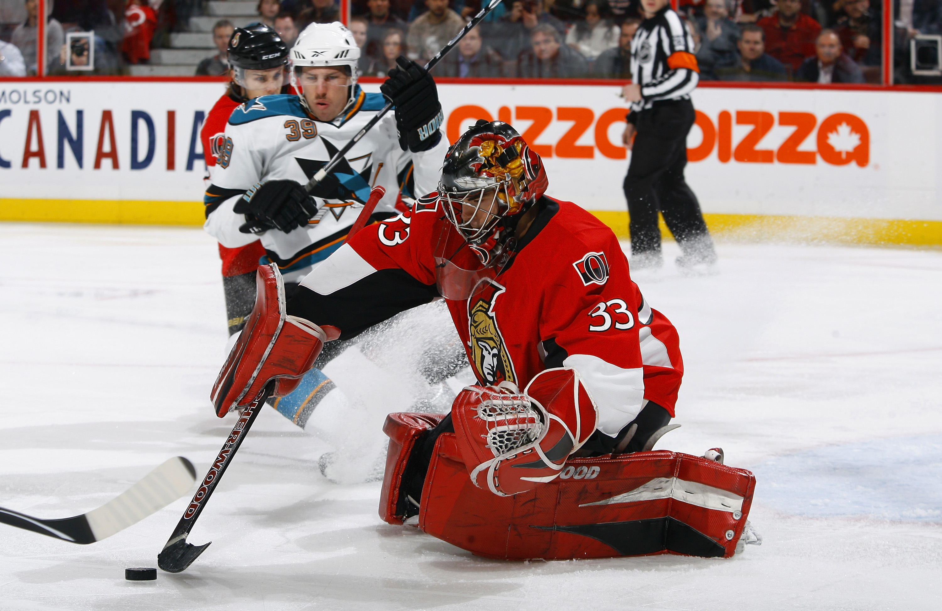 OTTAWA, ON - DECEMBER 02:  Pascal Leclaire #33 of the Ottawa Senators tries to control a rebound while Logan Couture #39 of the San Jose Sharks skates hard into the crease in a game at Scotiabank Place on December 2, 2010 in Ottawa, Ontario, Canada.  (Pho