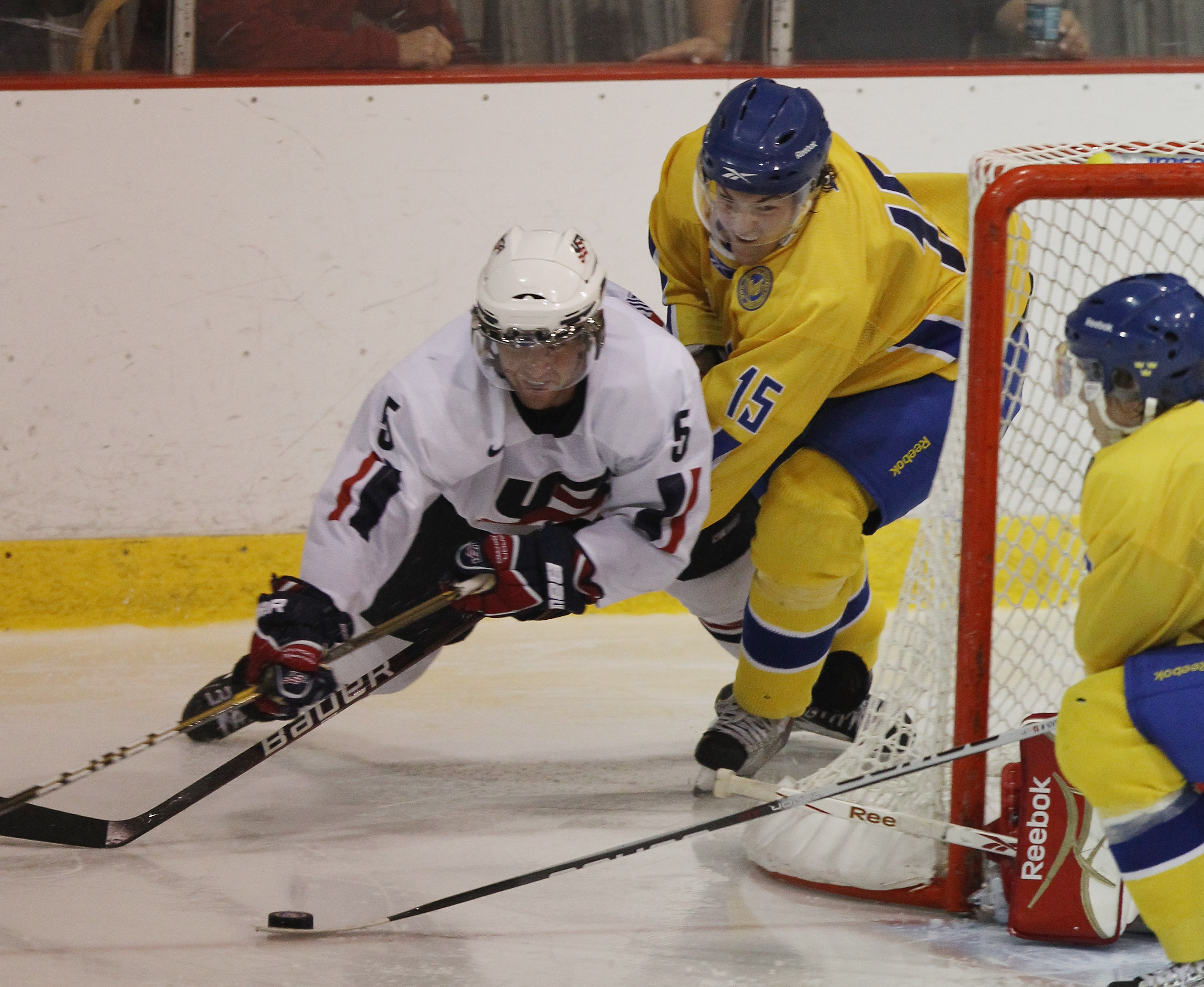 LAKE PLACID, NY - AUGUST 03: Simon Bertilsson #15  of Team Sweden trips up Kyle Palmieri #5 of Team USA at the USA Hockey National Evaluation Camp game on August 3, 2010 in Lake Placid, New York.  The USA defeated Sweden 6-3. (Photo by Bruce Bennett/Getty