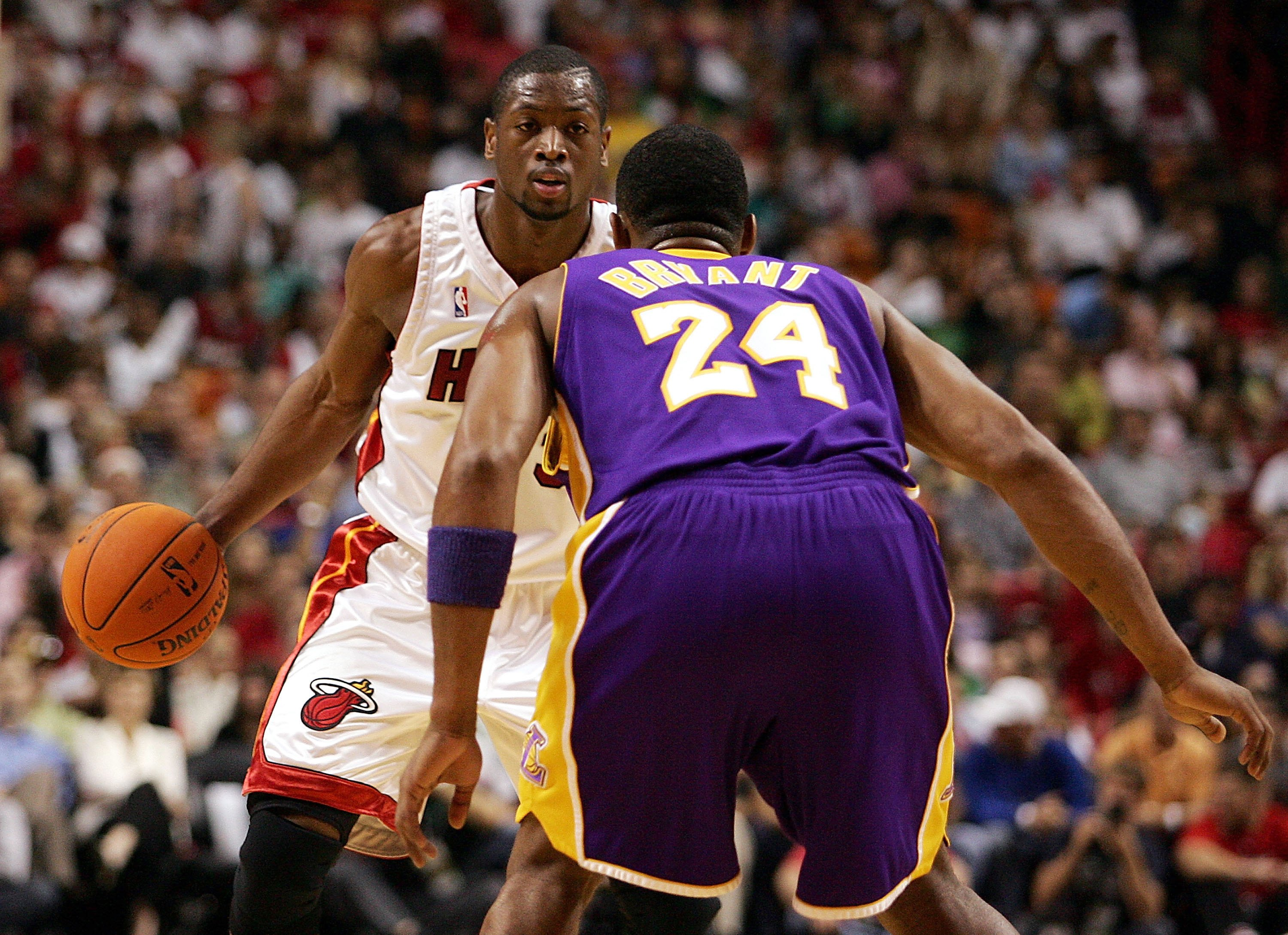 MIAMI - DECEMBER 25:  Guard Dwyane Wade #3 of the Miami Heat looks to drive against guard Kobe Bryant #24 of the Los Angeles Lakers on December 25, 2006 at the American Airlines Arena in Miami, Florida.  NOTE TO USER: User expressly acknowledges and agree