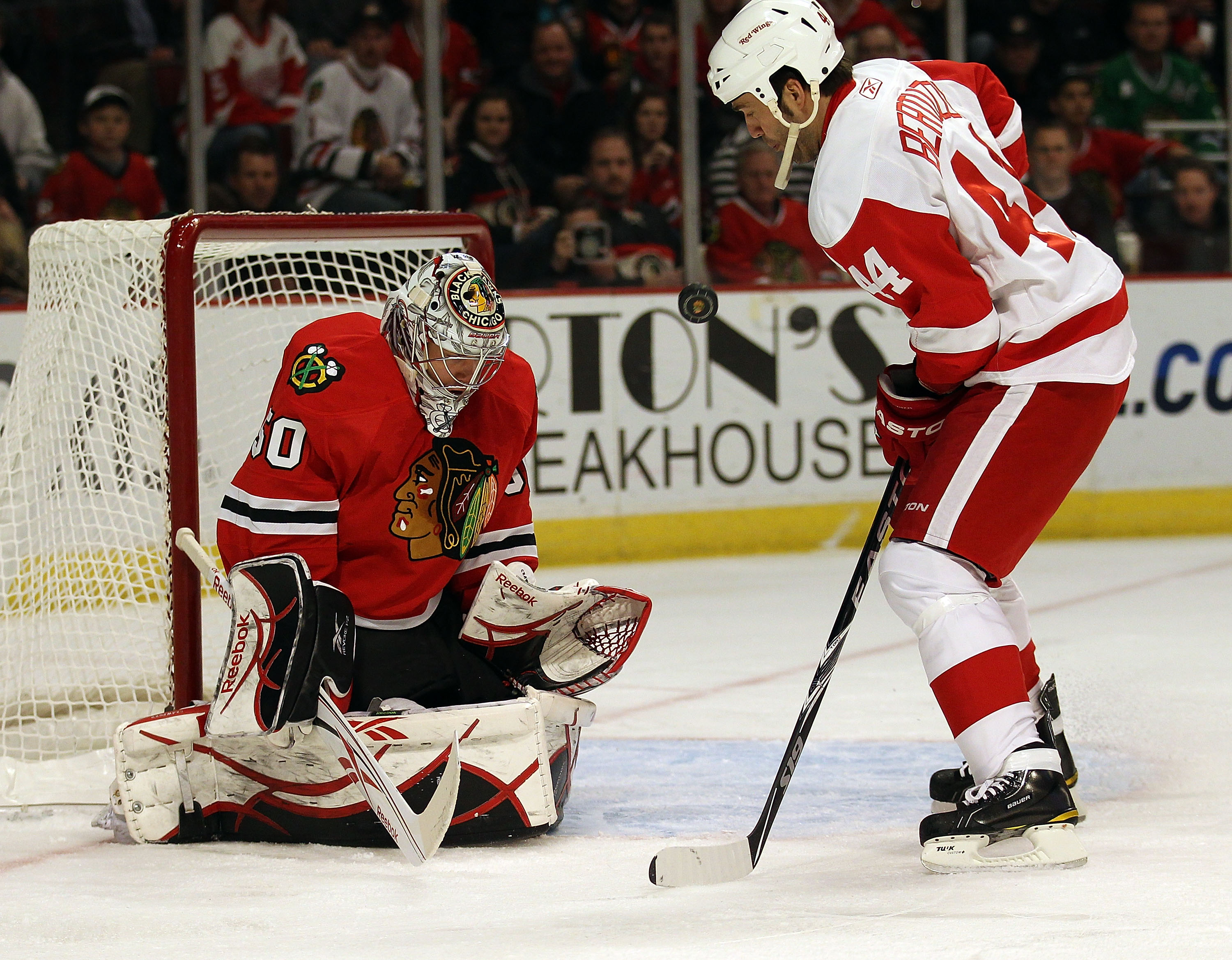 CHICAGO, IL - DECEMBER 17: Corey Crawford #50 of the Chicago Blackhawks makes a save and flips the puck in the air in front of Todd Bertuzzi #44 of the Detroit Red Wings at the United Center on December 17, 2010 in Chicago, Illinois. The Blackawks defeate