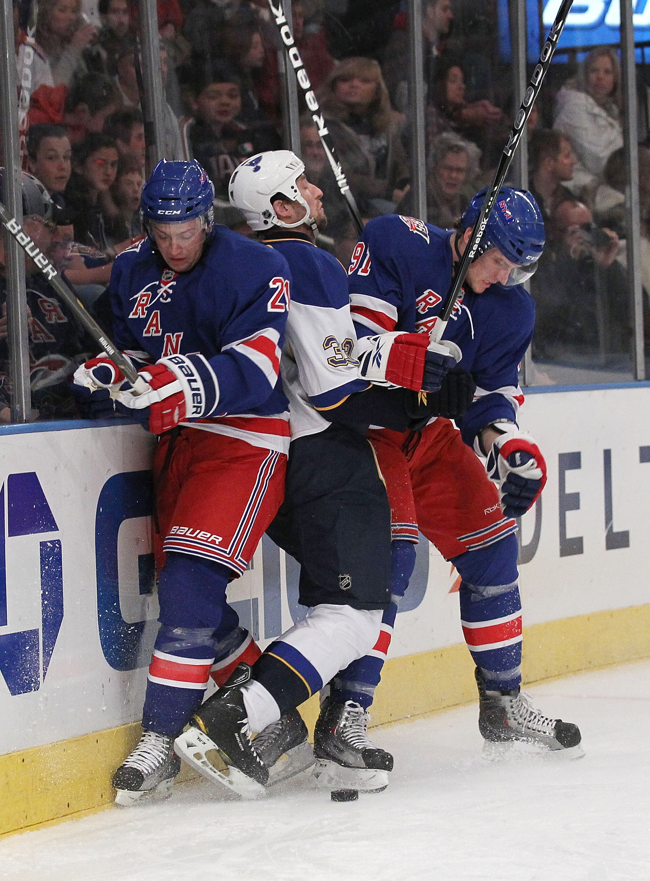 NEW YORK - NOVEMBER 07:  Derek Stephan #21 and Evgeny Grachev #91 of the New York Rangers sandwich Tyson Strachan #33 of the St. Louis Blues during their game on November 7, 2010 at Madison Square Garden in New York City, New York.  (Photo by Al Bello/Get