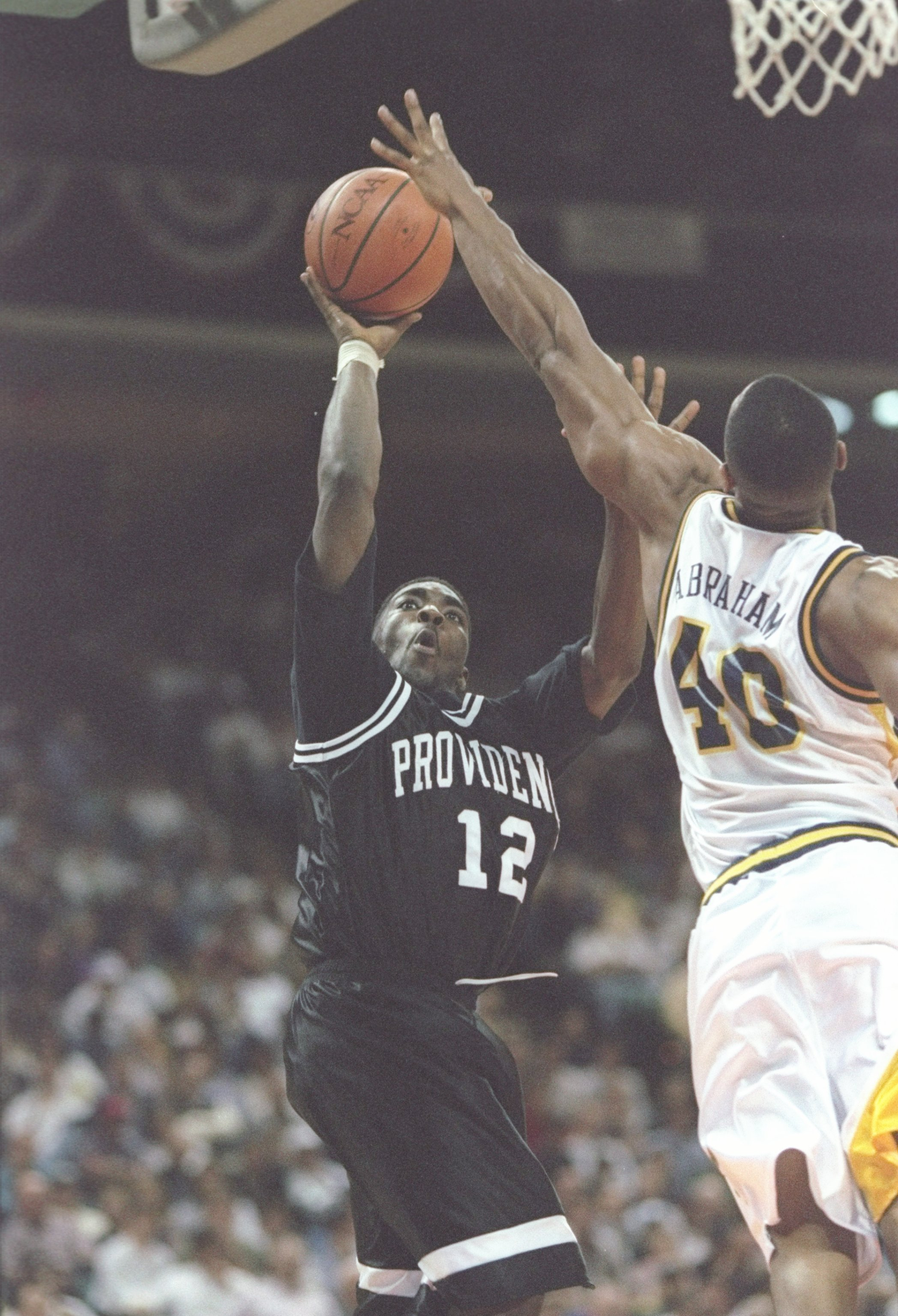 14 Mar 1997: Guard God Shammgod of the Providence Friars shoots a basket as forward Faisal Abraham of the Marquette Golden Eagles tries to block during a playoff game at the Charlotte Coliseum in Charlotte, North Carolina. The Friars won the game 81 - 59.