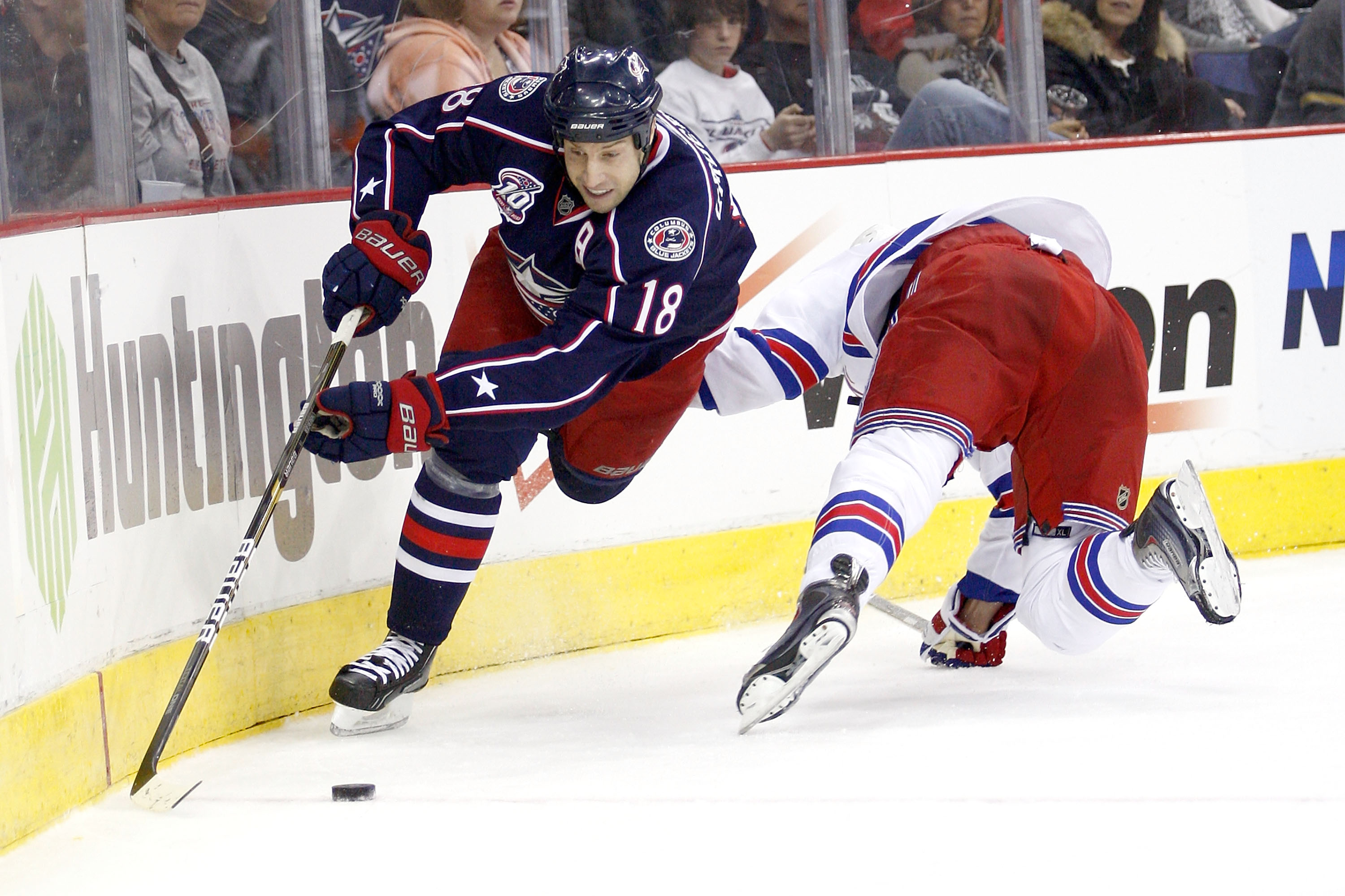 COLUMBUS,OH - DECEMBER 11:  R.J. Umberger #18 of the Columbus Blue Jackets slips past Marc Staal #18 of the New York Rangers to get to a loose puck during the second period on December 11, 2010 at Nationwide Arena in Columbus, Ohio.  (Photo by John Griesh