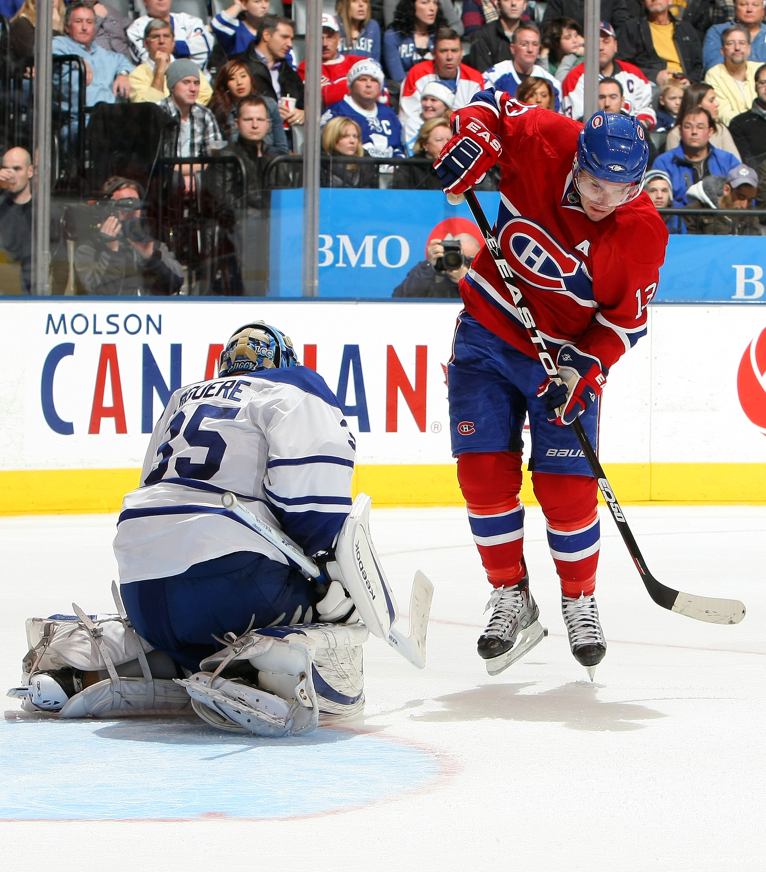 TORONTO - DECEMBER 11:  Mike Cammalleri #13 of the Montreal Canadiens leaps to avoid a shot as Jean-Sebastien Giguere #35 of the Toronto Maple Leafs makes a save during their NHL game at Air Canada Centre on December 11, 2010 in Toronto, Ontario, Canada.(