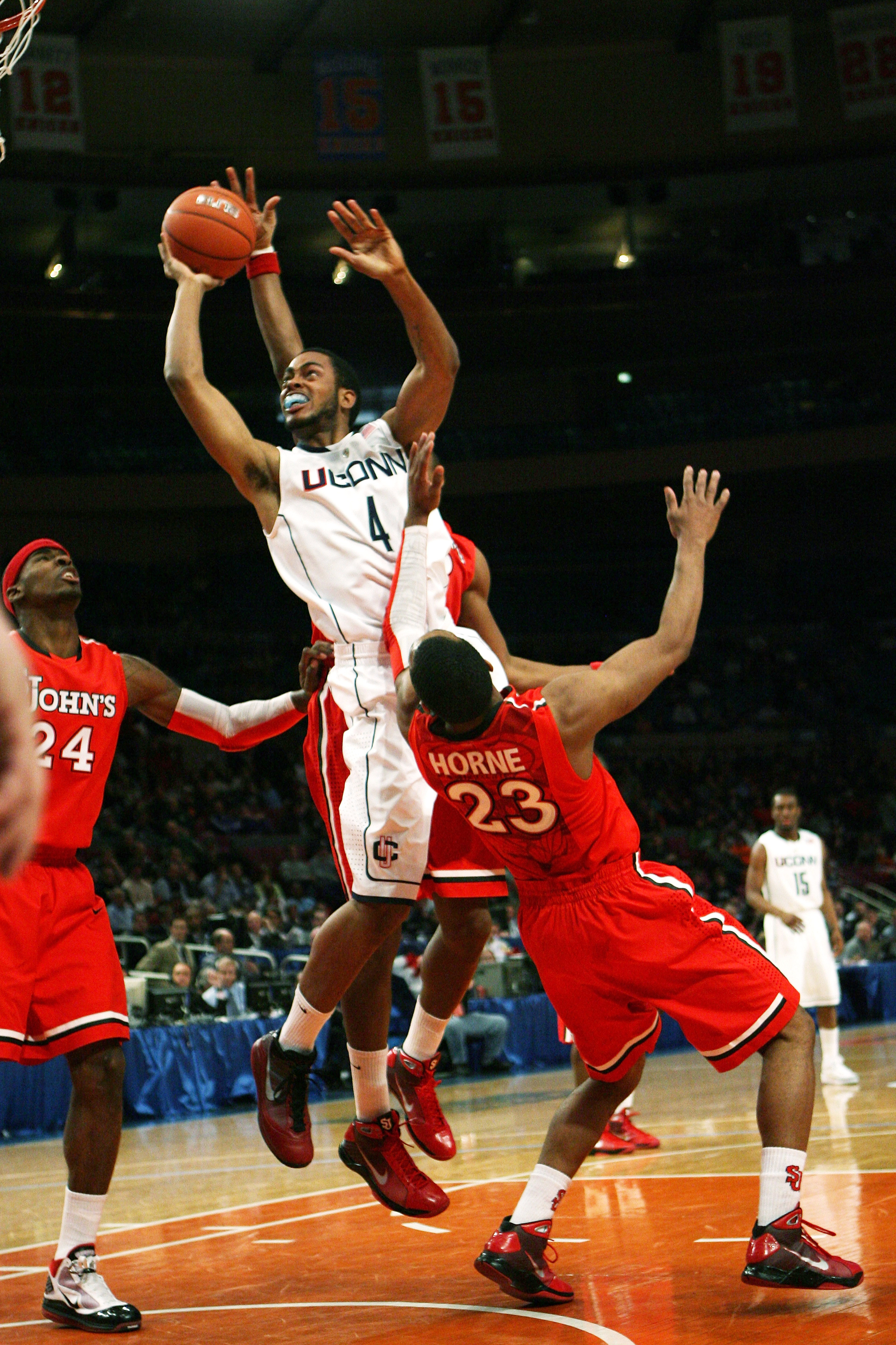 NEW YORK - MARCH 09: Jamal Coombs-McDaniel #4 the Connecticut Huskies drives to the basket over  Paris Horne #23 of the St. John's Red Storm at Madison Square Garden on March 9, 2010 in New York, New York. The Red Storm defeated the Huskies 73-51.  (Photo