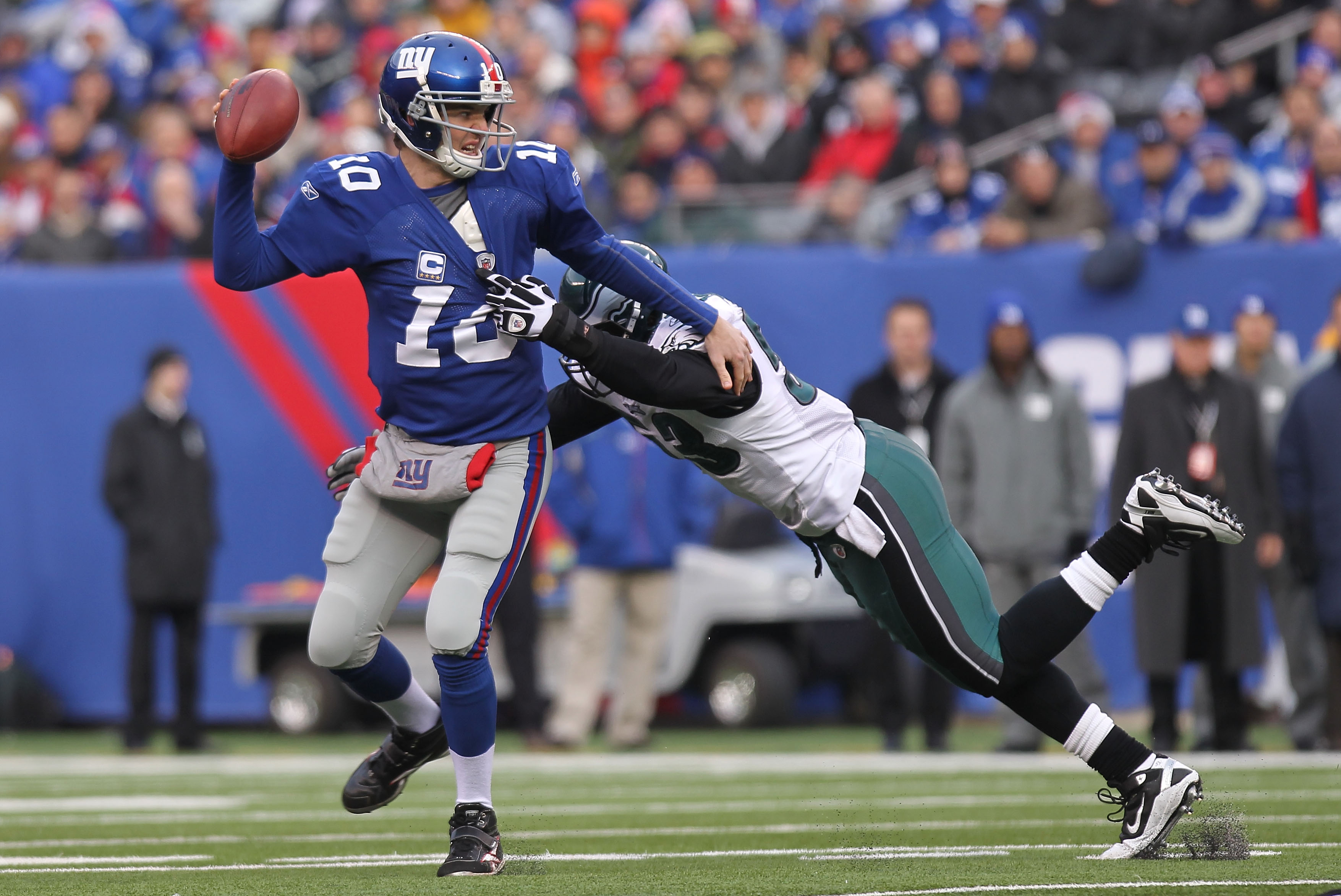EAST RUTHERFORD, NJ - DECEMBER 19:  Eli Manning #10 of the New York Giants is sacked by Moise Fokou #53 of the Philadelphia Eagles at New Meadowlands Stadium on December 19, 2010 in East Rutherford, New Jersey.  (Photo by Nick Laham/Getty Images)