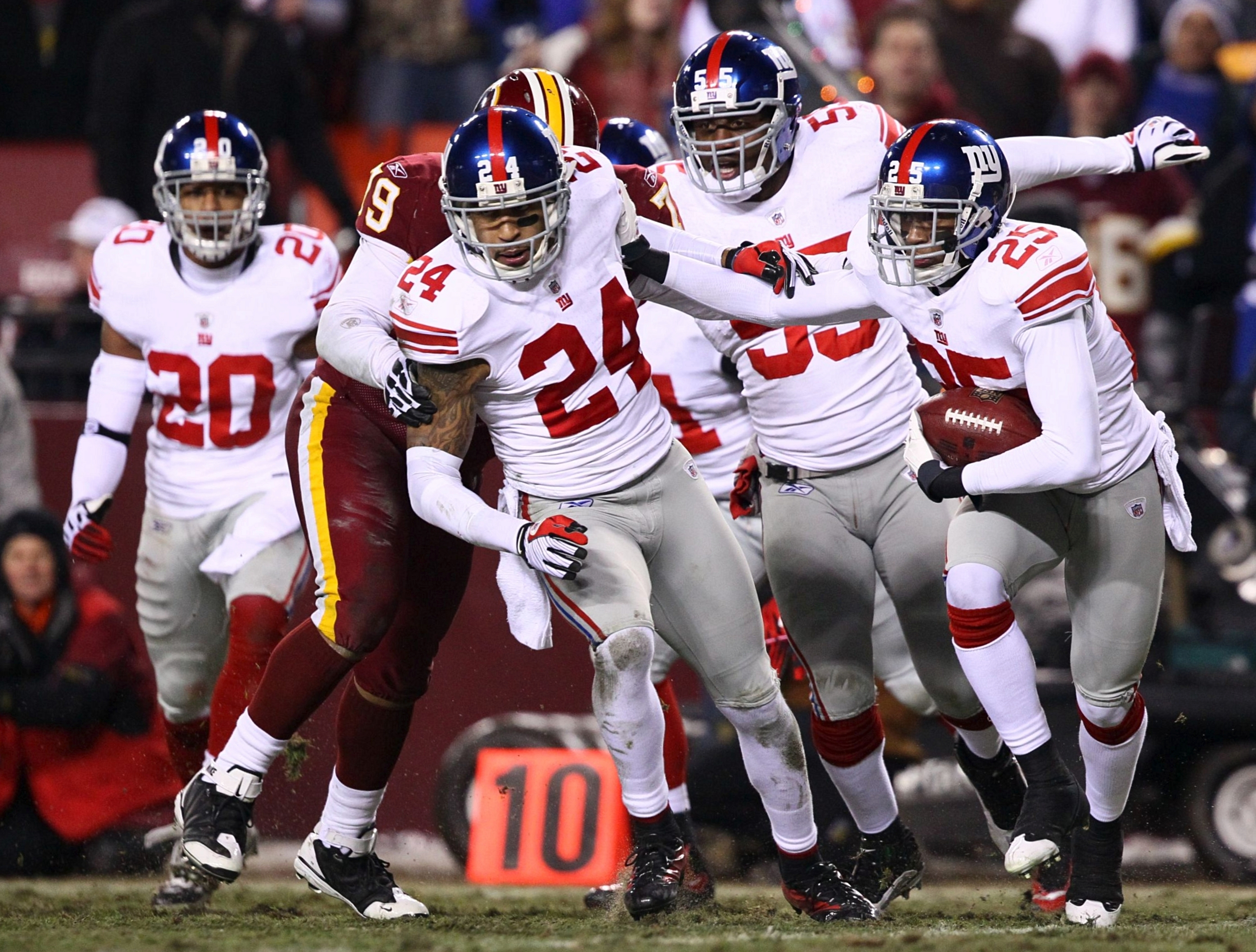 LANDOVER, MD - DECEMBER 21:  Cornerback Bruce Johnson #25 of the New York Giants runs with the ball after intercepting punter Hunter Smith #3 of the Washington Redskins at FedEx Field on December 21, 2009 in Landover, Maryland. (Photo by Win McNamee/Getty