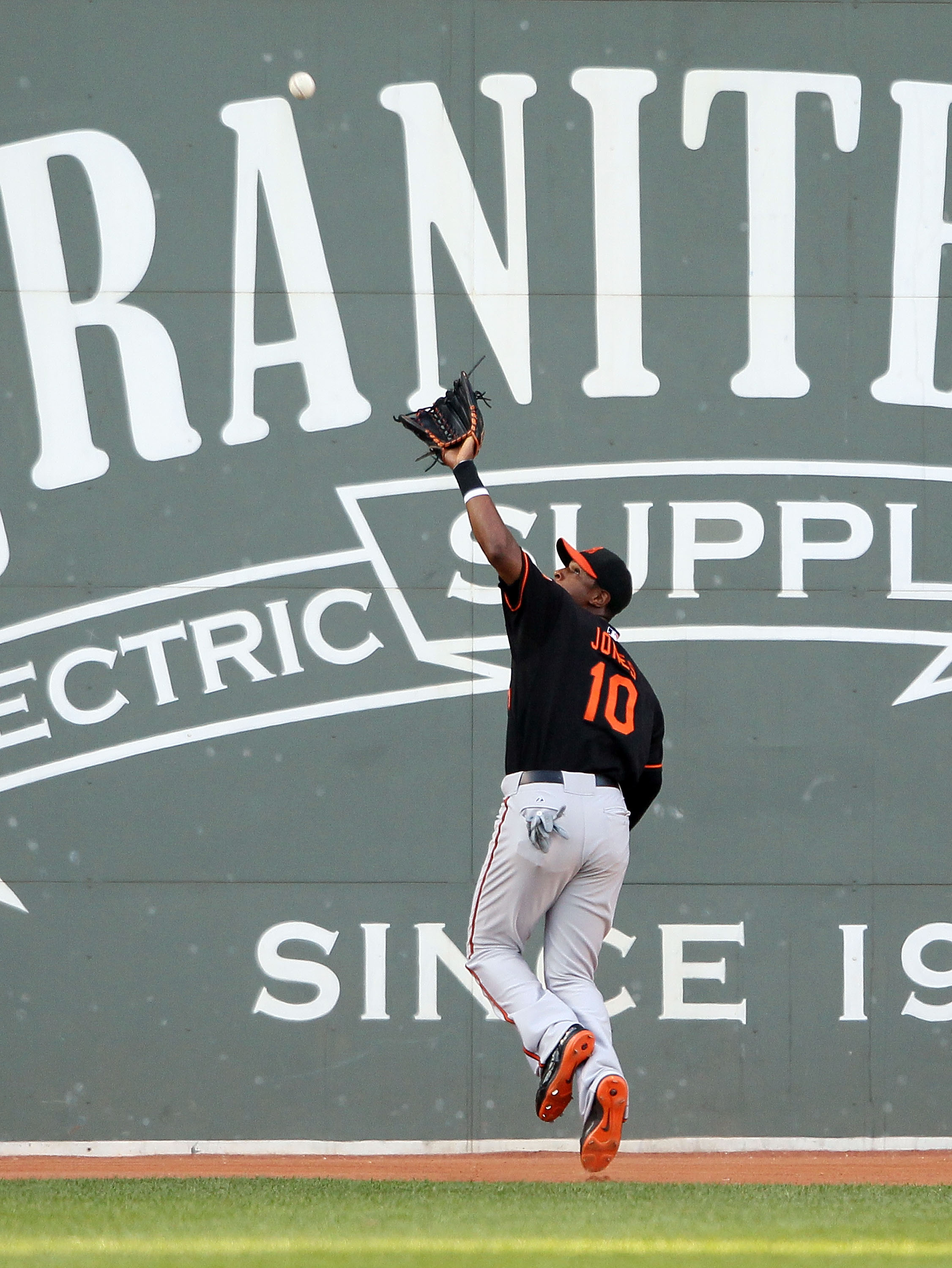 BOSTON - JULY 02:  Adam Jones #10 of the Baltimore Orioles makes the catch for the out on a hit by Eric Patterson of the Boston Red Sox on July 2, 2010 at Fenway Park in Boston, Massachusetts.  (Photo by Elsa/Getty Images)