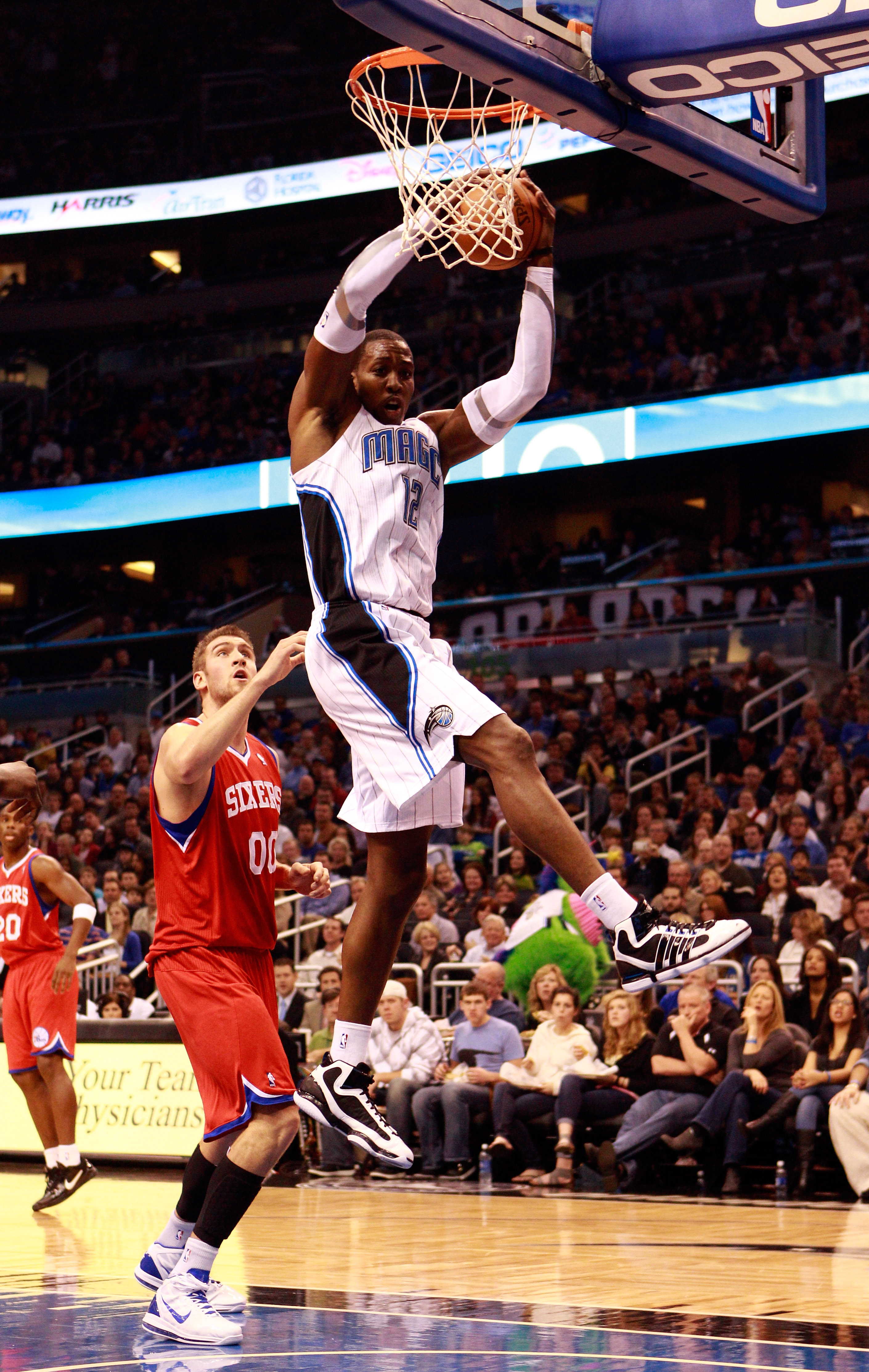 ORLANDO, FL - DECEMBER 18:  Dwight Hoawrd #12 of the Orlando Magic grabs a rebound over Spencer Hawes #00 of the Philadelphia 76ers during the game at Amway Arena on December 18, 2010 in Orlando, Florida.  NOTE TO USER: User expressly acknowledges and agr