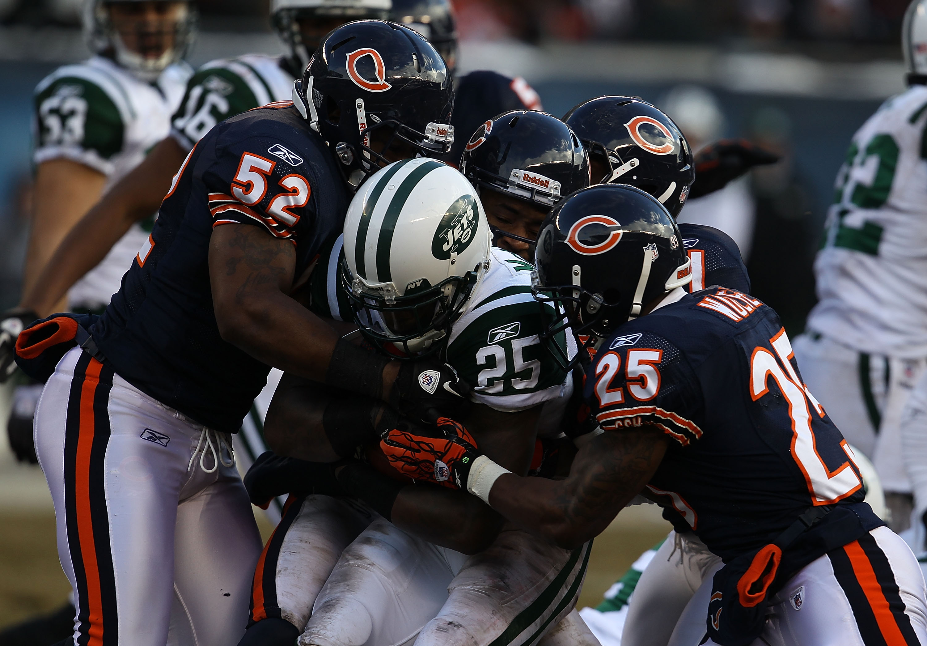 CHICAGO, IL - DECEMBER 26: Joe McKnight #25 of the New York Jets is tackled by Brian Iwuh #52, Rashied Davis #81, Corey Graham #21 and Garrett Wolfe #25 of the Chicago Bears at Soldier Field on December 26, 2010 in Chicago, Illinois. The Bears defeated th